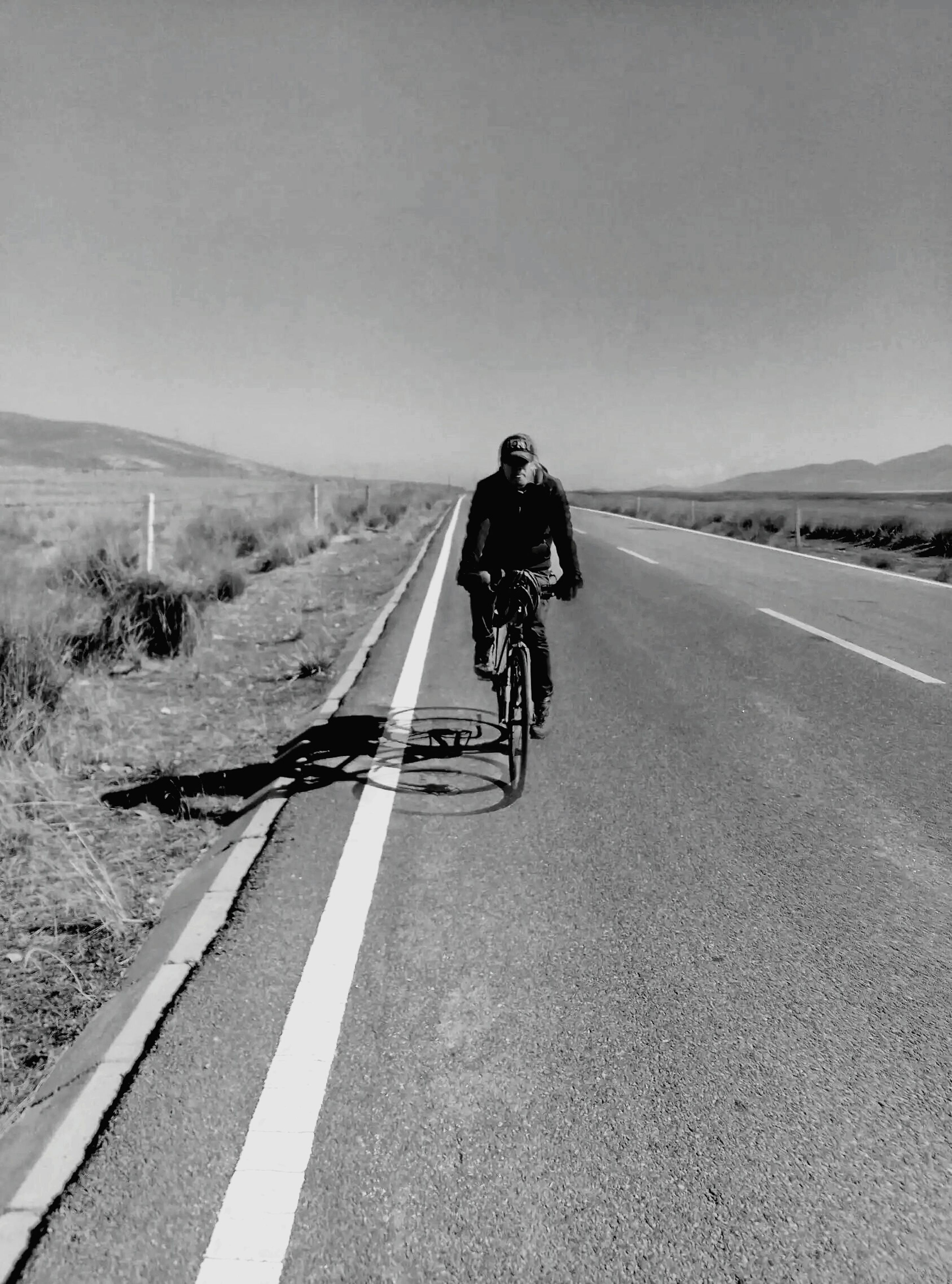 transportation, one person, riding, road, bicycle, landscape, full length, headwear, desert, helmet, outdoors, land vehicle, men, day, real people, sky, arid climate, adventure, sport, clear sky, mountain, nature, cycling helmet, one man only, biker, adult, young adult, people, adults only