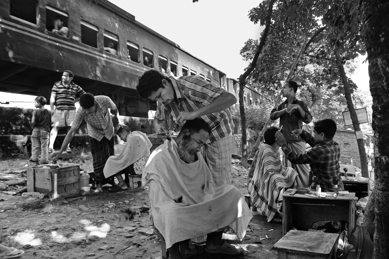 Lower income people preparing themselves and getting hair cut in an open place under a banyan tree for coming Eid-ul-Adha in couple of days. Eid Mubarak Large Group Of People Men Side View Full Length Street Standing Small Business Outdoors Street Market Train Travel Eiduladha Nikon Dhaka, Bangladesh EyeEm Bangladesh EyeEm Best Shots