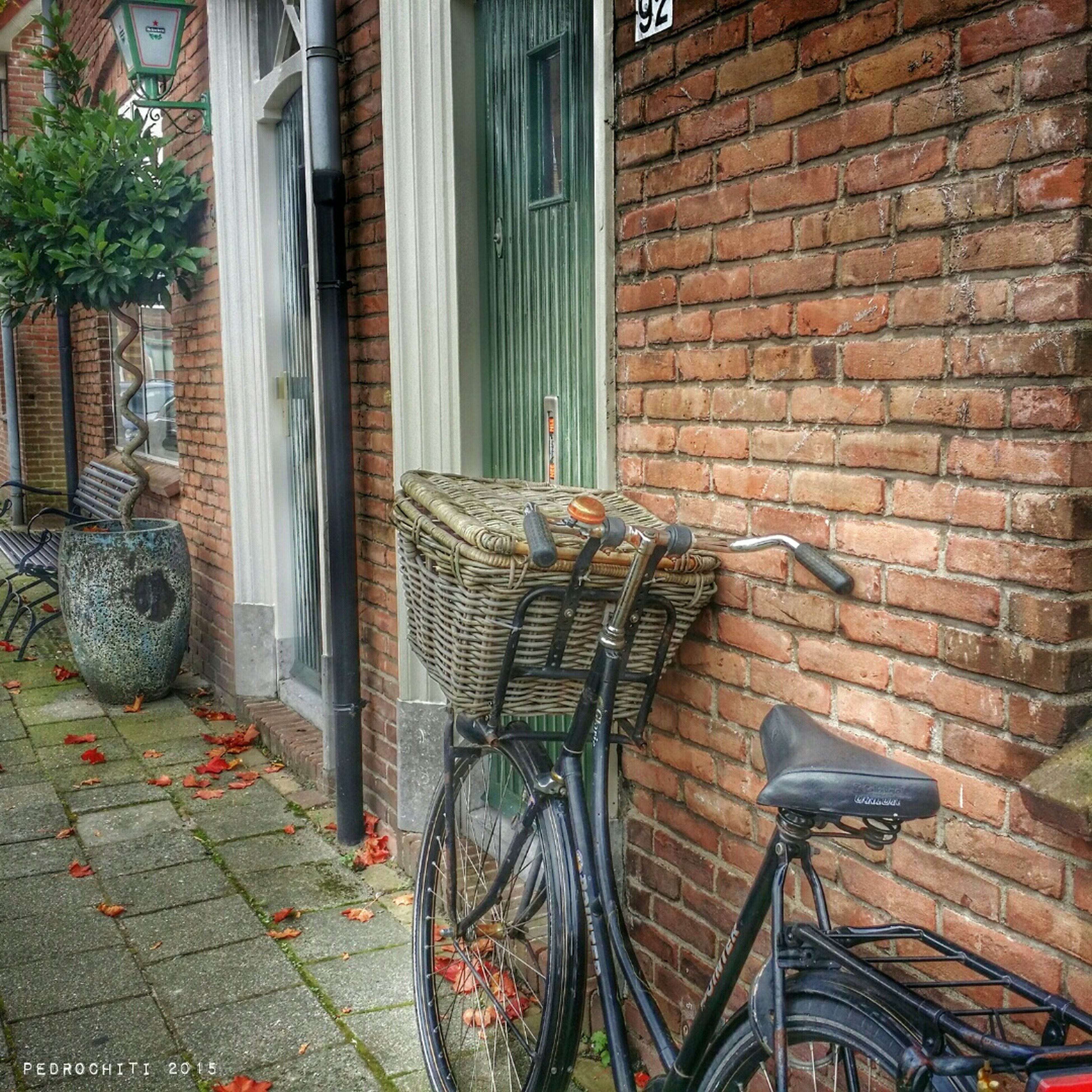 building exterior, architecture, built structure, brick wall, wall - building feature, building, window, bicycle, wall, house, cobblestone, sidewalk, residential structure, outdoors, day, residential building, stone wall, street, no people, transportation