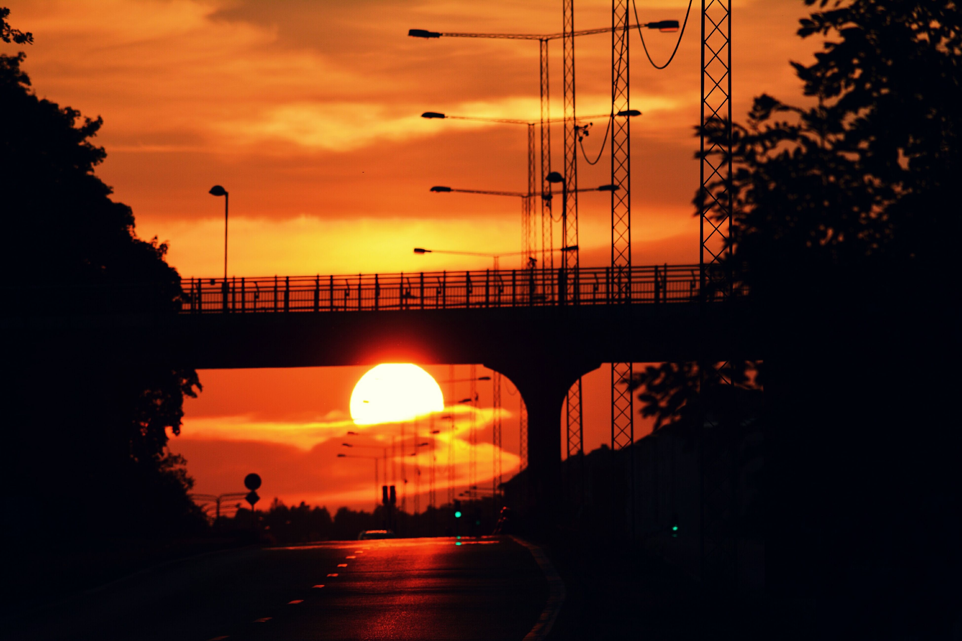 sunset, silhouette, orange color, transportation, sky, car, tree, street light, road, cloud - sky, land vehicle, connection, mode of transport, sun, the way forward, nature, street, power line, electricity pylon, beauty in nature