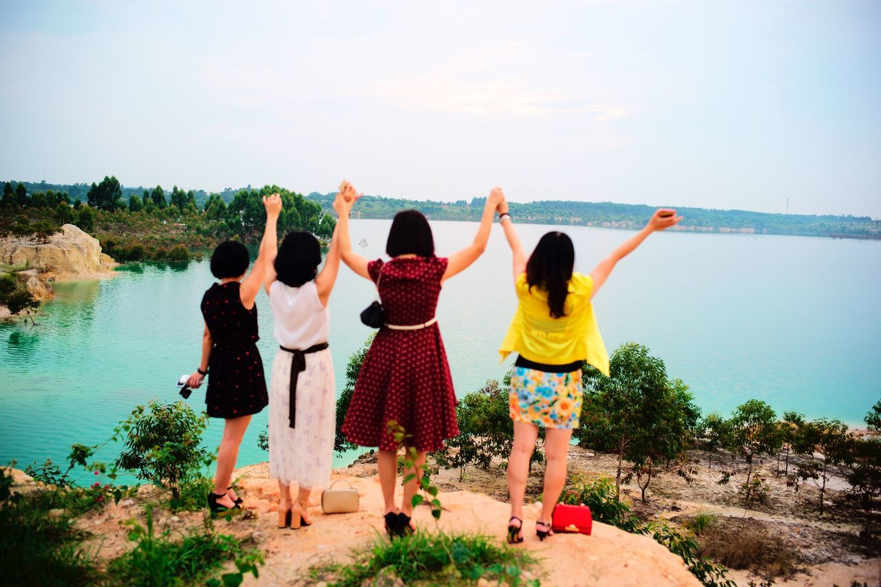 Arms Raised Real People Rear View Togetherness Day Standing Full Length Fun Sky Leisure Activity Friendship Outdoors Clear Sky Water Childhood Vacations Nature Tree People