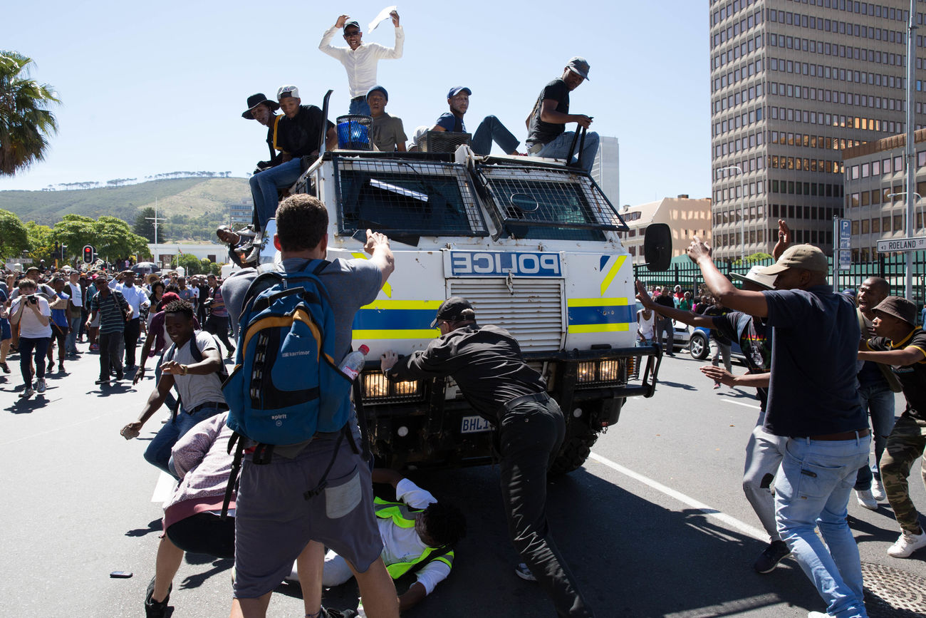 A RG-12 Nyala amoured police vehicle trying to shake students from its roof nearly runs over a protestor from the Fees Must Fall Movement. Moments earlier a black sign was slid between the steel cage and the windscreen blocking the drivers view. 28th October 2016 Cape Town Feesmustfall Outdoors Police Force Real People South Africa The Photojournalist - 2017 EyeEm Awards