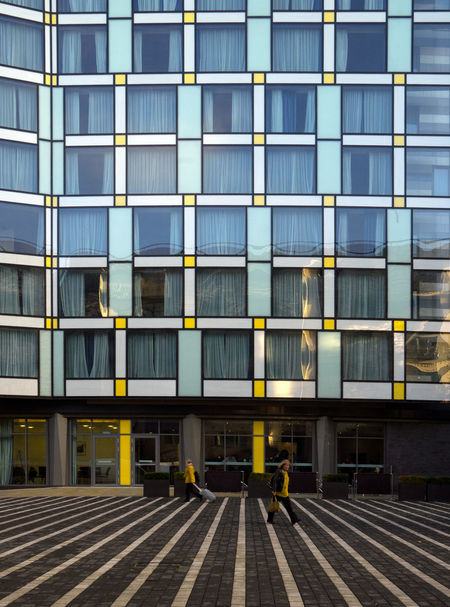 2 Women Architecture Building Exterior Built Structure City Colour Coordinated Day Geometric Hotel Modern Opposite Directions Outdoors Pattern People Walking  Yellow Paint The Town Yellow
