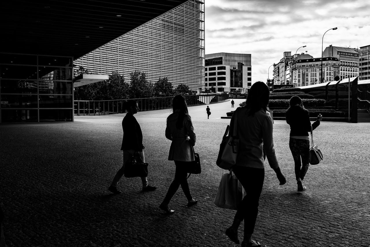 real people, architecture, built structure, building exterior, walking, lifestyles, full length, rear view, women, leisure activity, togetherness, city life, men, city, day, outdoors, childhood, friendship, sky, adult, people