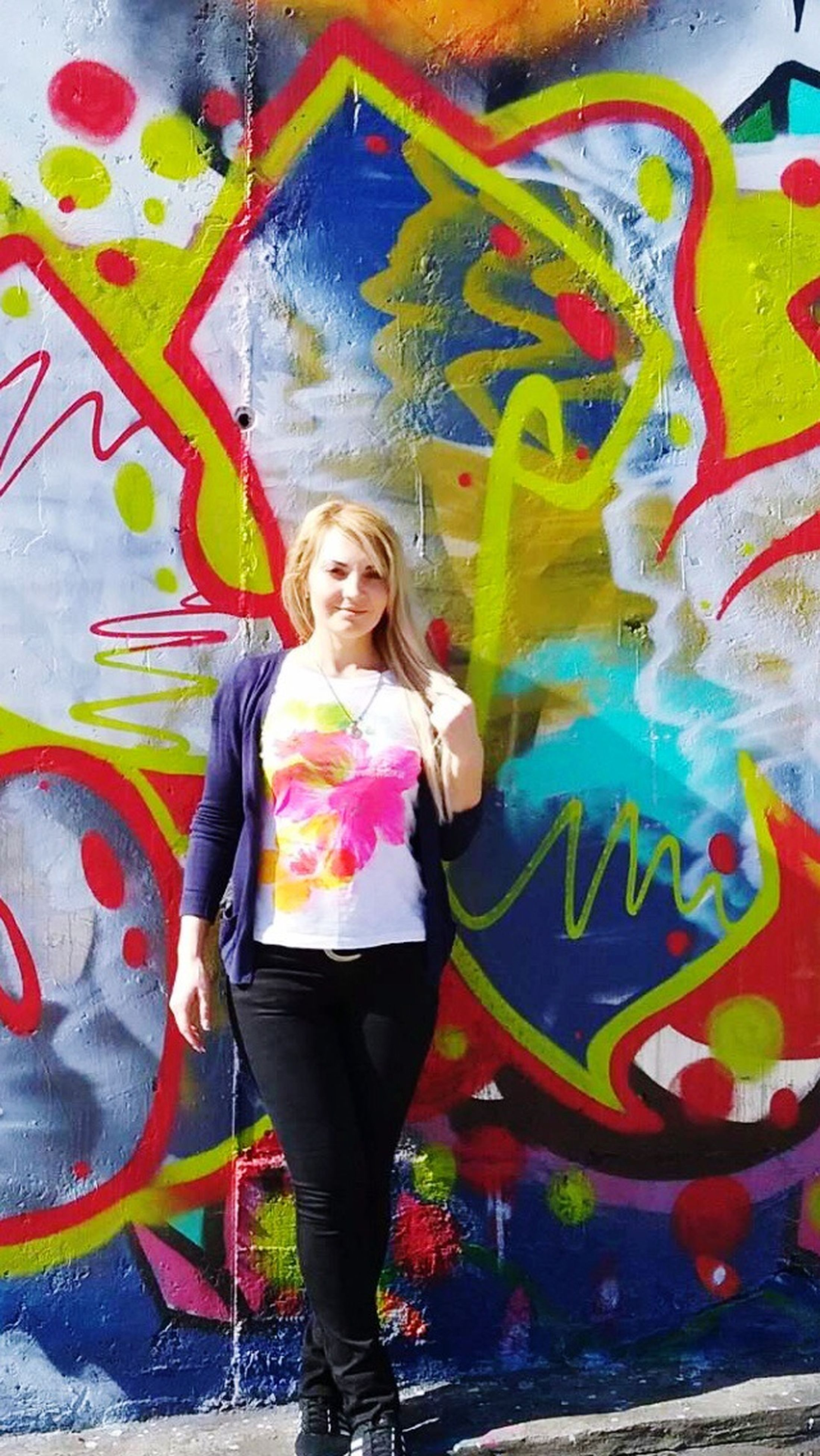 multi colored, graffiti, art, lifestyles, creativity, casual clothing, art and craft, wall - building feature, leisure activity, standing, front view, person, looking at camera, three quarter length, portrait, childhood, full length, smiling