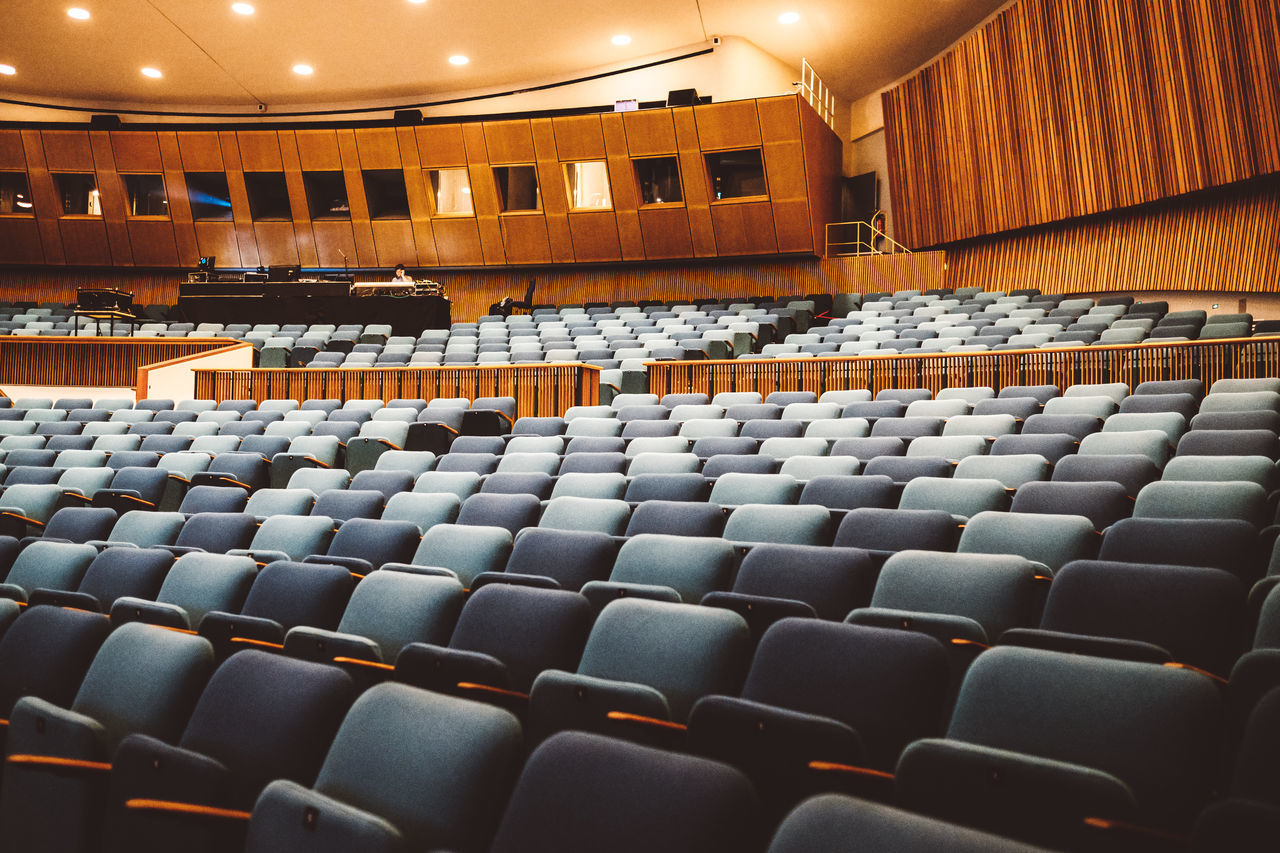 seat, arts culture and entertainment, chair, auditorium, movie theater, stage theater, music, stage - performance space, in a row, performing arts event, no people, movie, event, indoors, film industry, concert hall, nightlife, bleachers, performance, architecture
