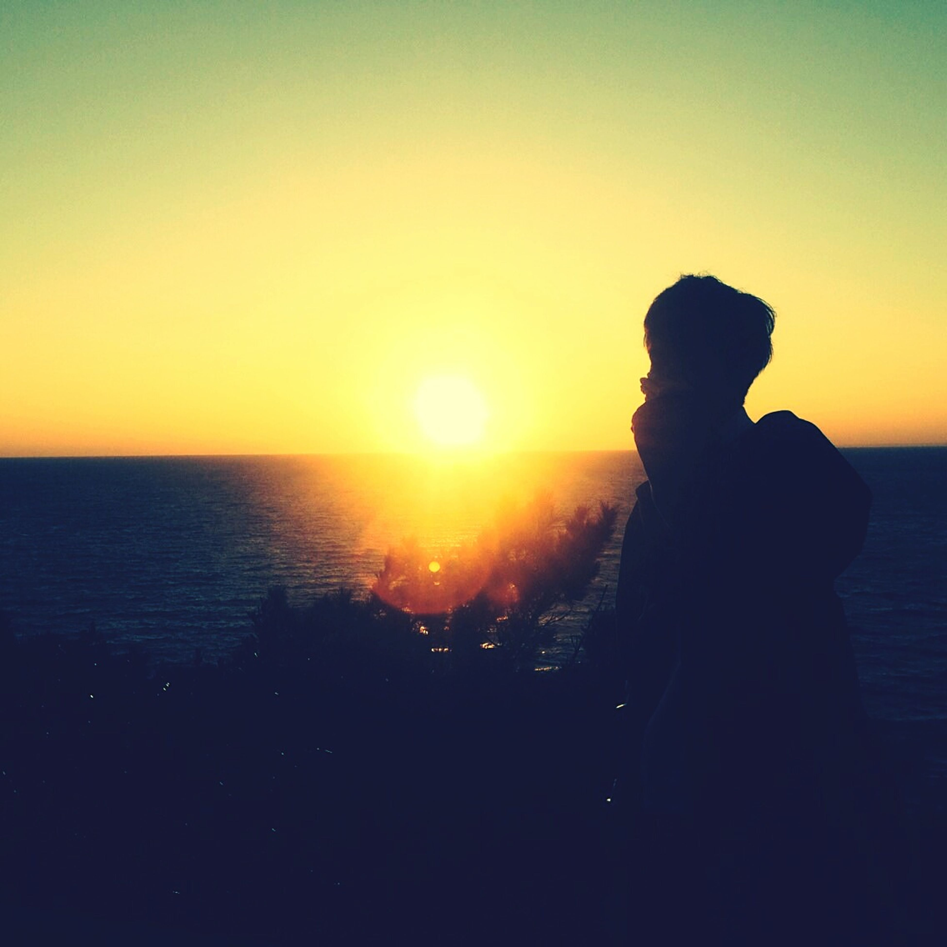 sunset, sea, horizon over water, sun, water, silhouette, leisure activity, lifestyles, orange color, scenics, beauty in nature, standing, tranquil scene, beach, person, tranquility, sky, rear view