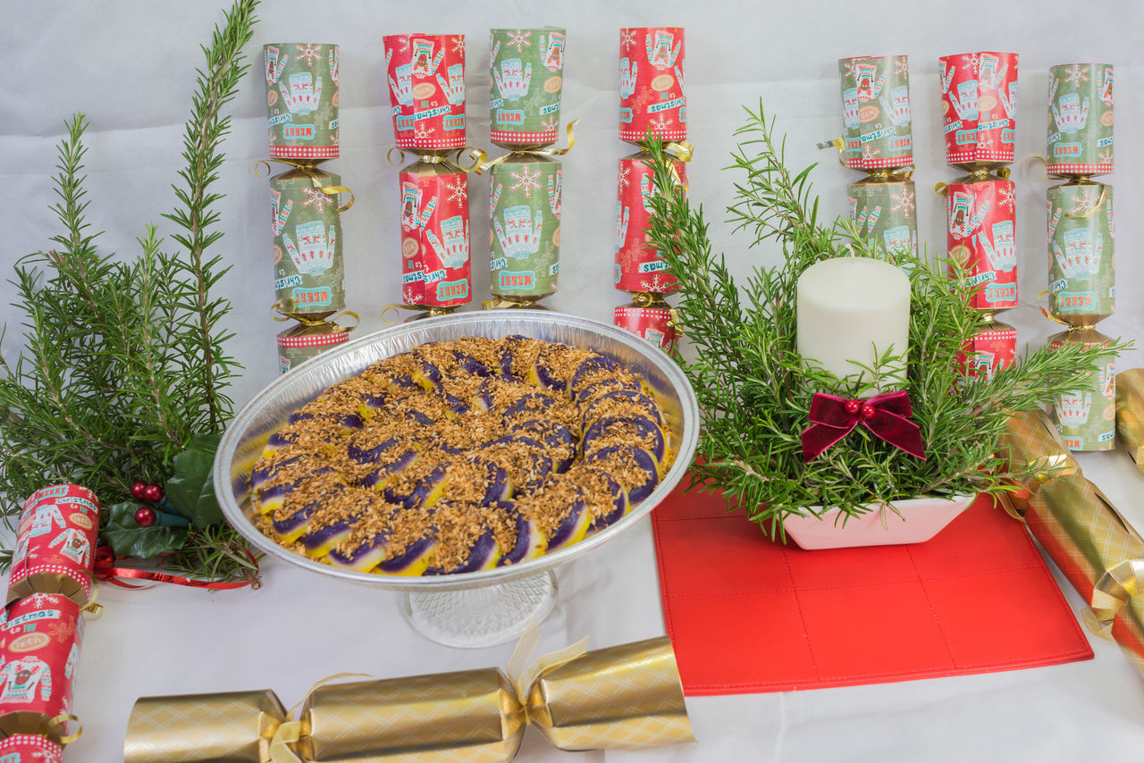 A display for christmas purple yam sweets filipino style plus candle and crackers with evergreen leaves Christmas Crackers Day Evergreen Green Color High Angle View Indoors  Leaf No People Purple Yam Sweets Filipino Red Table Mat Table White Back Drop