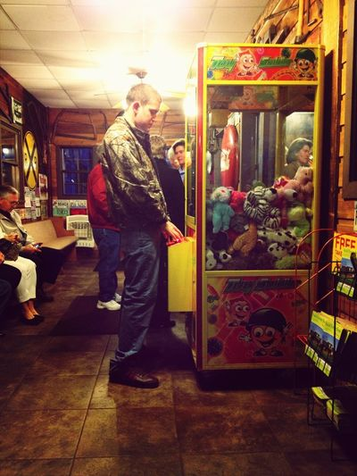He's playing the claw machine lol(: