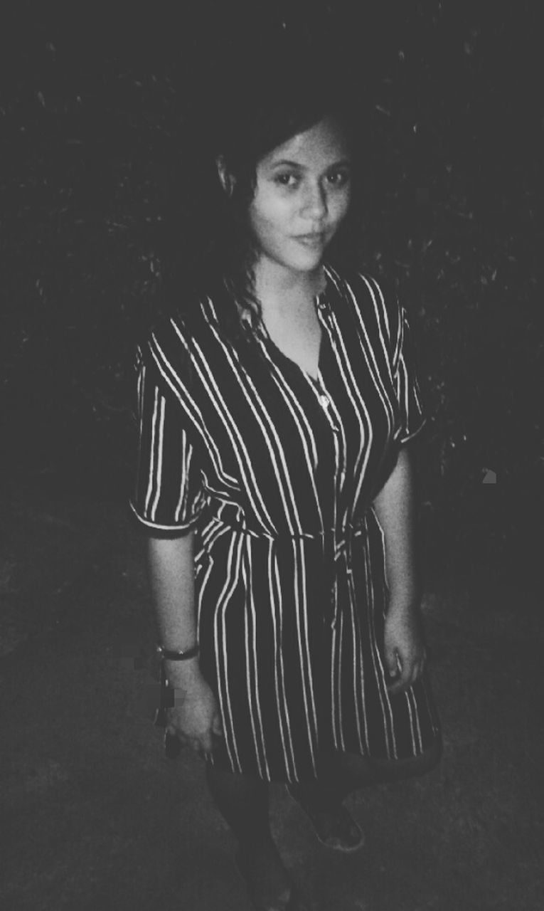 one person, young adult, looking at camera, standing, real people, night, portrait, lifestyles, young women, outdoors, people