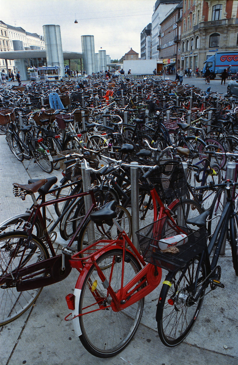 bicycle, mode of transport, land vehicle, building exterior, architecture, stationary, transportation, built structure, day, parking, city, outdoors, bicycle rack, sky, no people