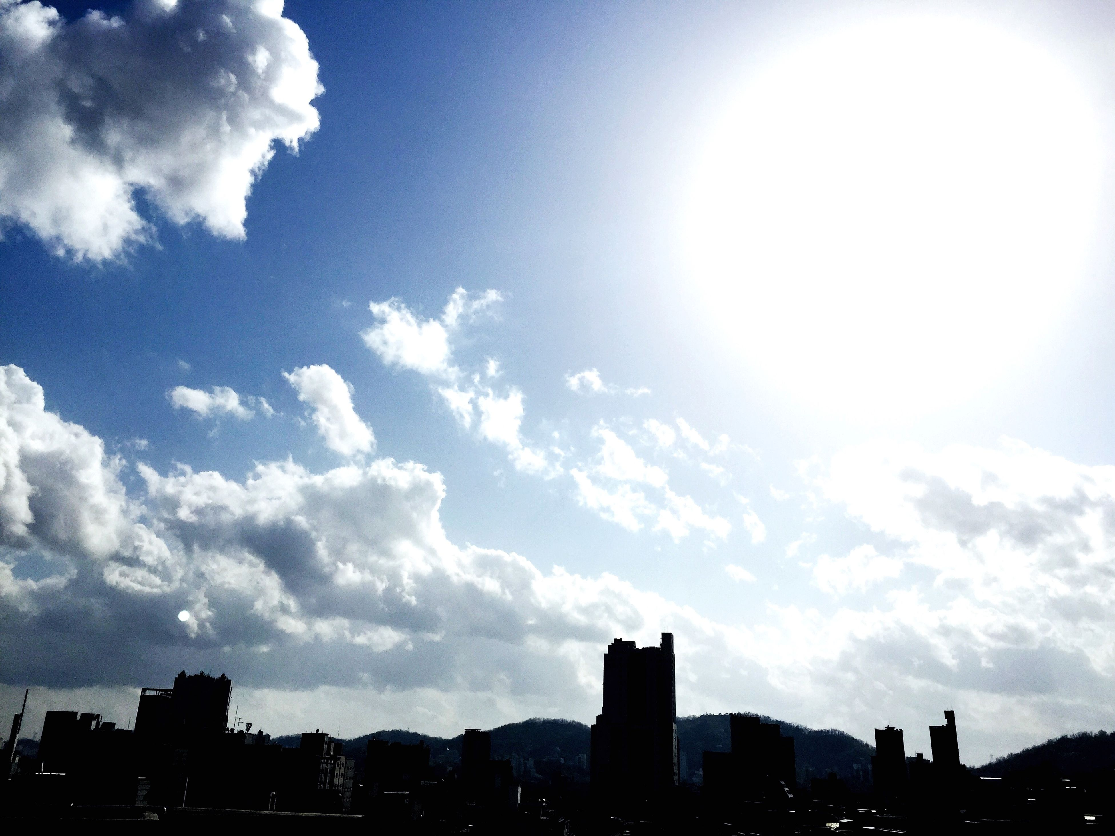 building exterior, architecture, built structure, city, sky, silhouette, skyscraper, sun, cityscape, sunbeam, sunlight, cloud - sky, low angle view, urban skyline, cloud, building, outdoors, skyline, tall - high, office building