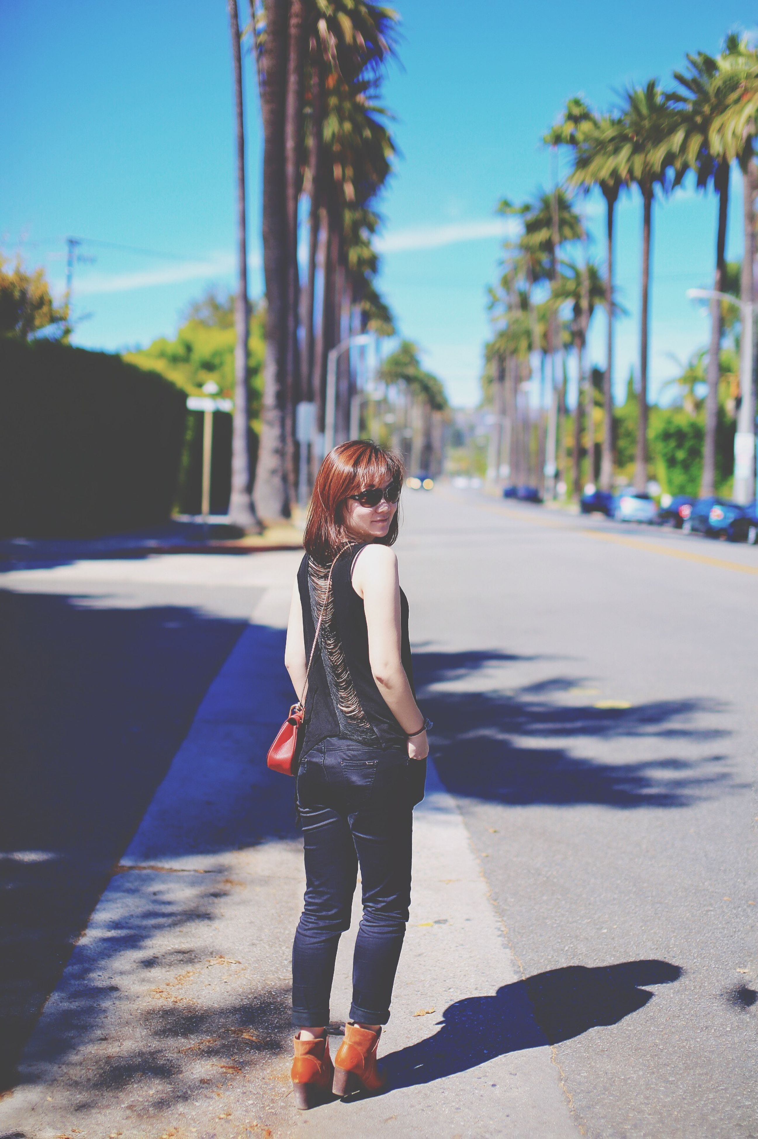 street, shadow, casual clothing, sunlight, leisure activity, road, lifestyles, sunny, transportation, focus on foreground, tree, the way forward, day, long hair, young adult, outdoors