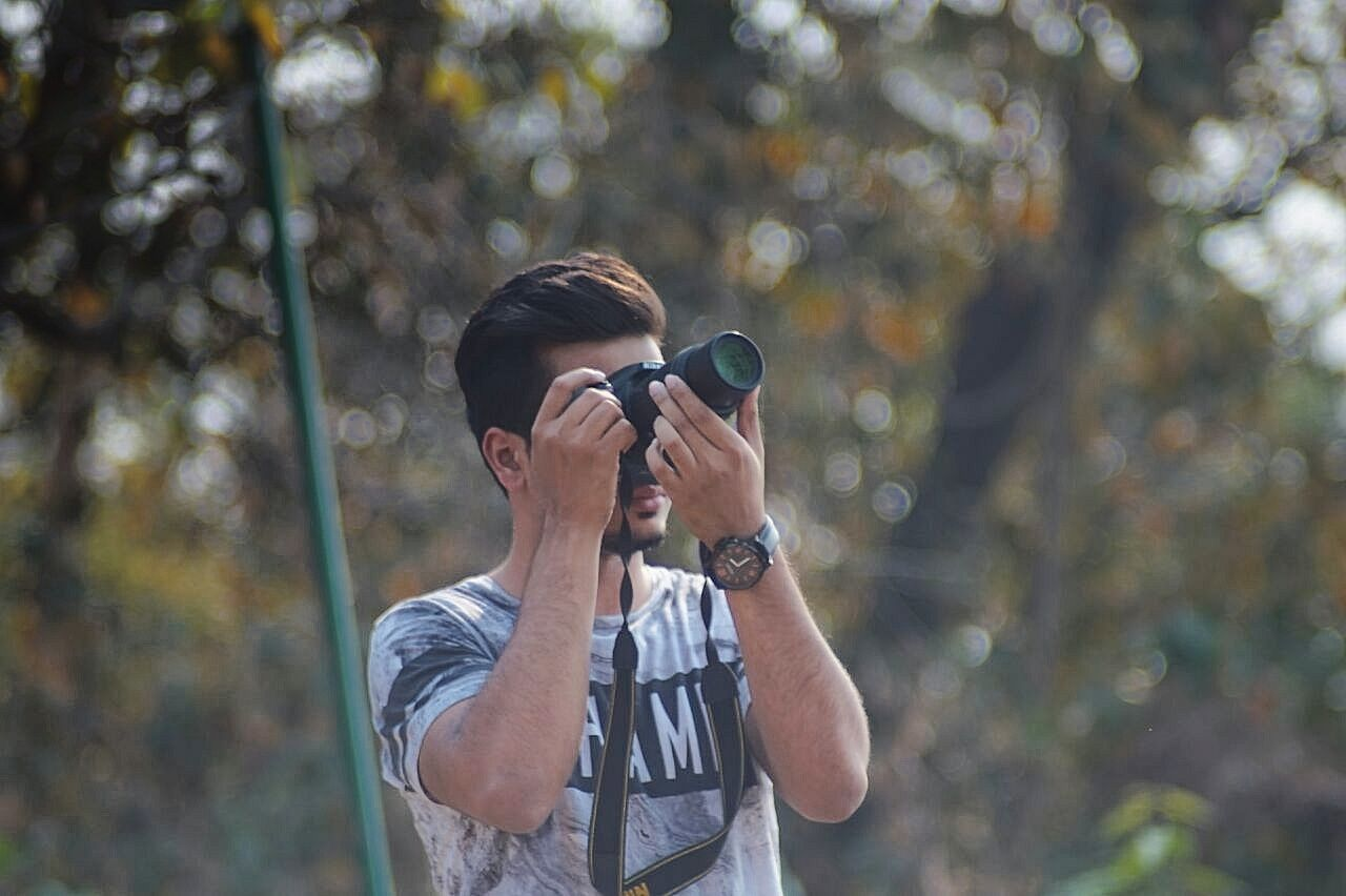 Photography Themes Photographing Camera - Photographic Equipment Portable Information Device Holding Photographer Outdoors Adult Technology Day Adults Only Tree Digital Camera Men Only Men One Person Nature People One Man Only