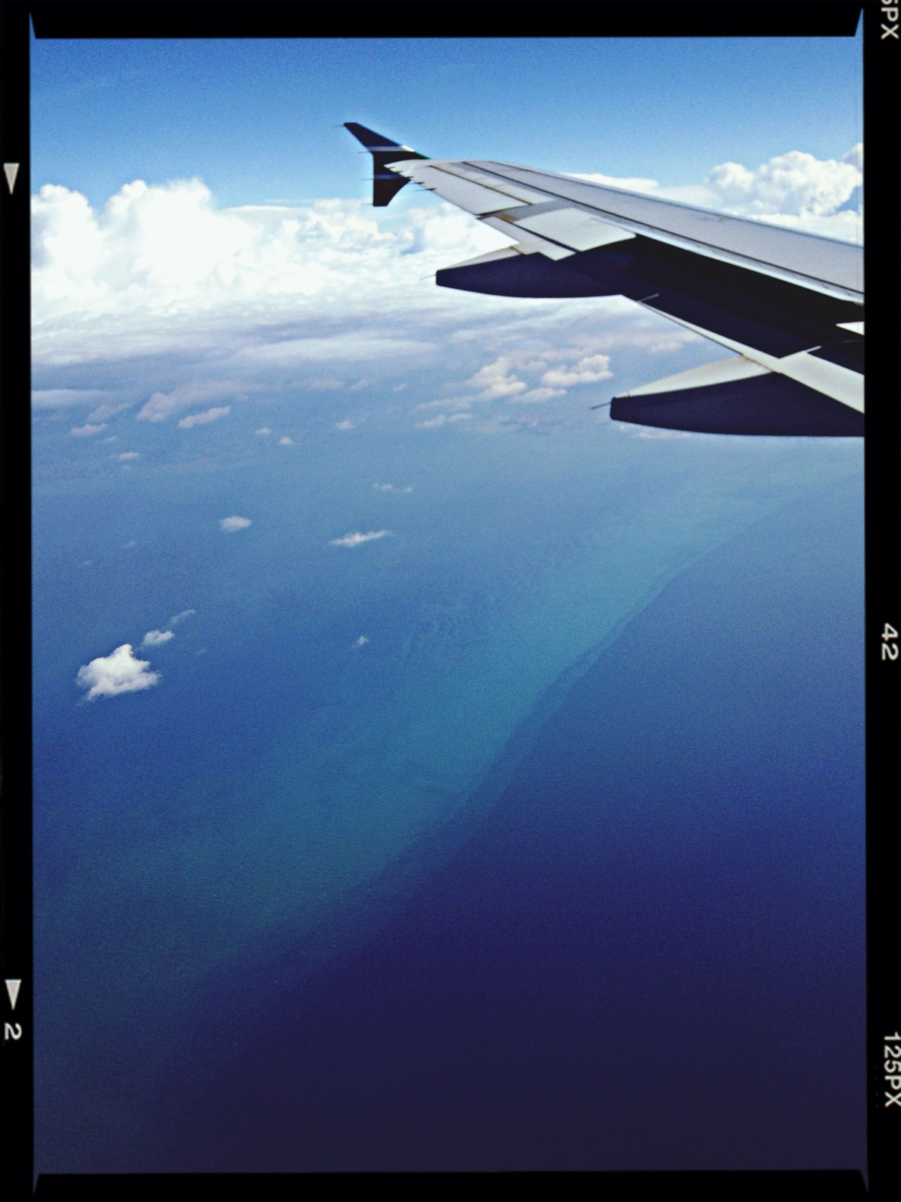 aircraft wing, airplane, flying, sky, air vehicle, transportation, aerial view, cloud - sky, scenics, beauty in nature, transfer print, blue, part of, cloud, nature, mid-air, tranquil scene, mode of transport, tranquility, landscape
