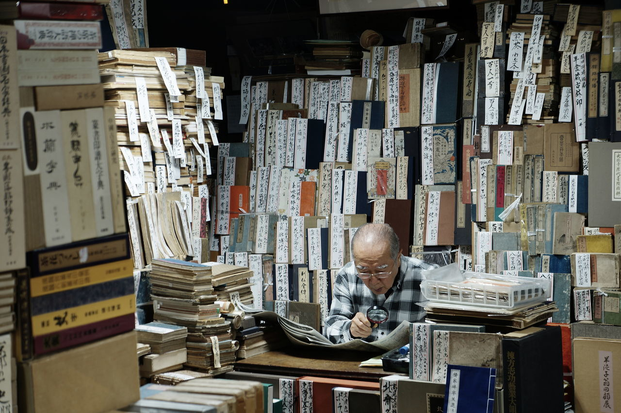 book, one person, large group of objects, indoors, stack, abundance, bookshelf, senior adult, real people, shelf, table, senior men, one senior man only, men, arrangement, choice, standing, one man only, library, eyeglasses, day, only men, adult, people