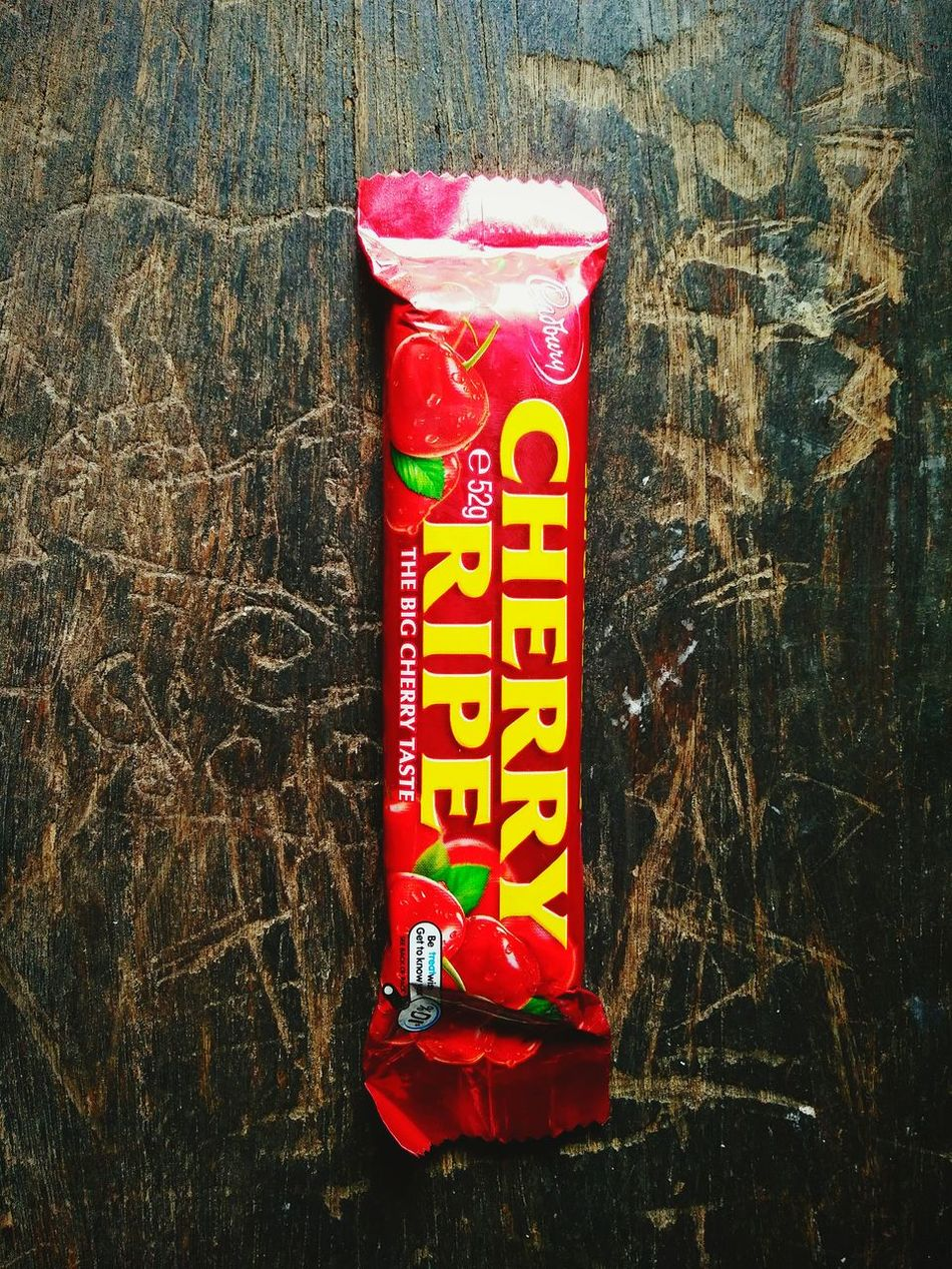 The awesome cherry ripe lolly on the wooden table with all beautiful words and art on it. Sweet Food Lolly Yummy♡ Cherry Unopened Can't Wait To Open Lolly Lol :) Beautiful Photo 👌 No People No One Around Marco Photography Wooden Texture Wooden Table Wooden Art