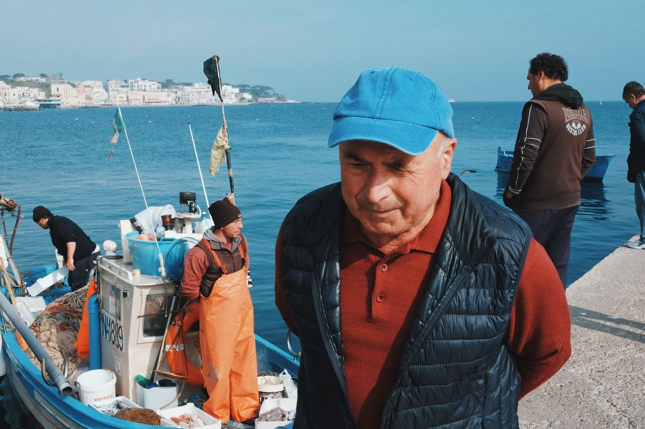 real people, sea, senior men, senior adult, standing, cap, outdoors, day, men, lifestyles, nautical vessel, water, sky, horizon over water, nature, one person