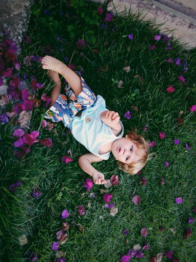 High Angle View Real People Baby Day One Person Grass Flower Happiness Growth People Lifestyles Tree Smiling Babies Only Happiness Backgrounds Playing Sitting Elementary Age Pink Color Nature Freshness Childhood Full Frame Cute