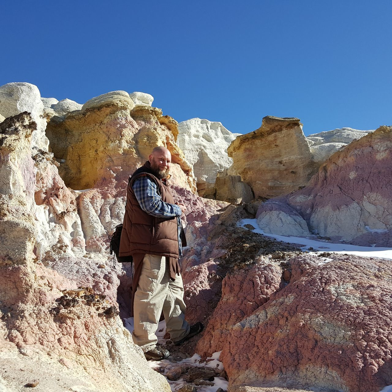 One Man Surrounded By Rocks AGAINST CLEAR BLUE SKY