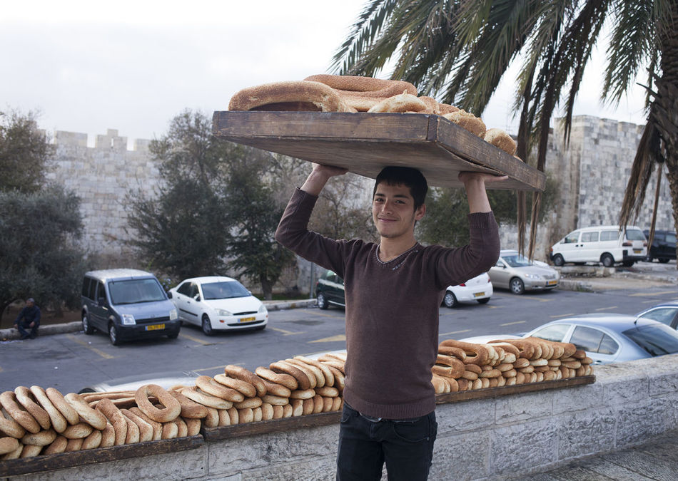 Young man is preparing beigeles for sale at the Damascus Gate, Jerusalem Baking Beigel Bread Casual Clothing City Commercial Day Happiness Israel Jerusalem Leisure Activity Lifestyles Local Looking At Camera Middle East Old City Outdoors Pastry Person Sale Selling Smile Smiling Young Adult First Eyeem Photo