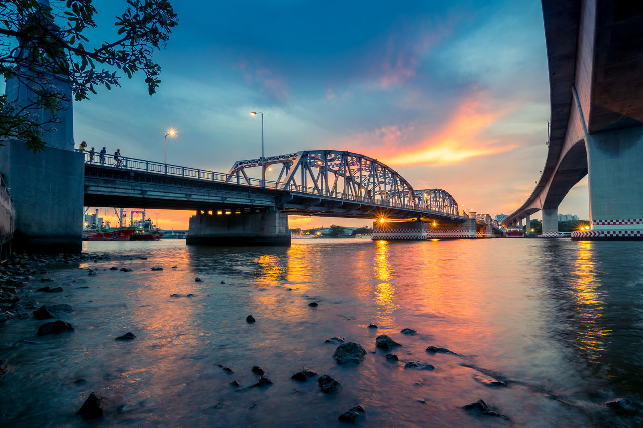Bangkok bridge in bangkok , Thailand at twilight Arch Bridge Architecture Bridge Built Structure City Cloud Cloud - Sky Connection Engineering Illuminated Long Nature No People Orange Color Outdoors Rippled River Sky Sunset SUPPORT Suspension Bridge Tourism Travel Destinations Water