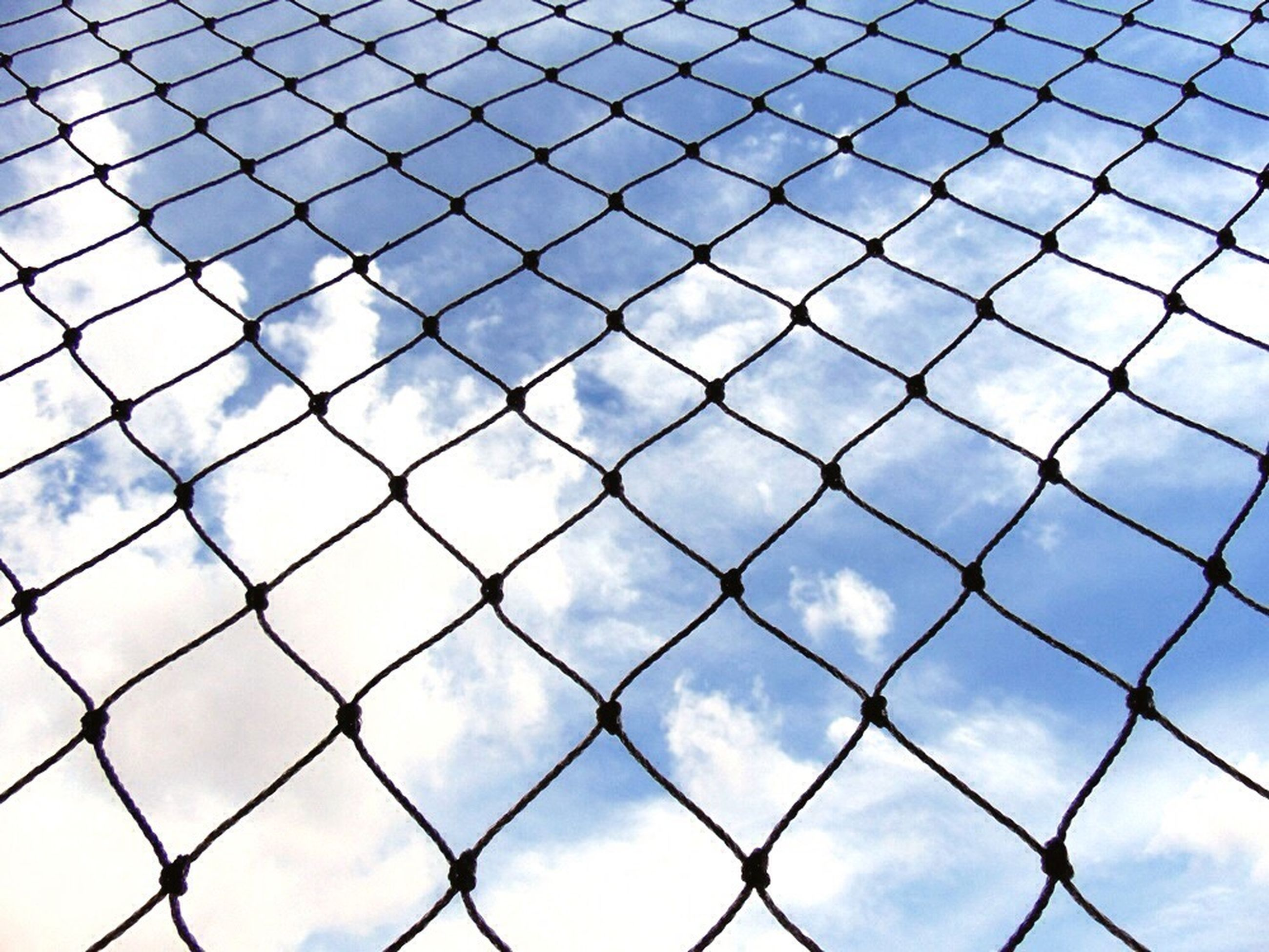full frame, chainlink fence, cloud - sky, sky, backgrounds, fence, safety, protection, pattern, cloudy, security, metal, day, low angle view, cloud, blue, outdoors, no people, city, built structure