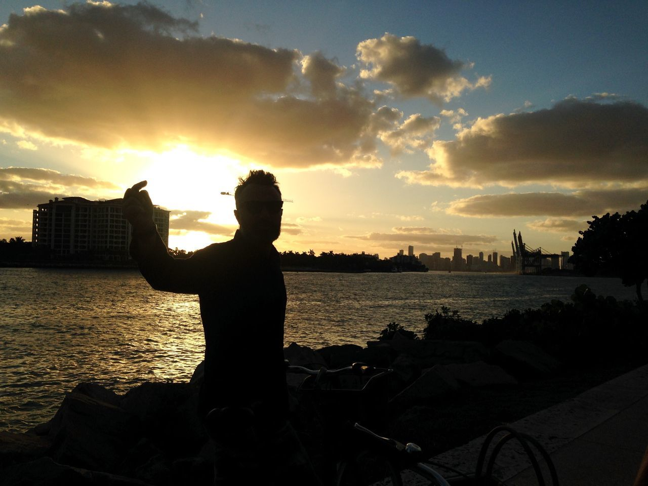 sunset, building exterior, architecture, built structure, water, one person, city, sky, river, cityscape, outdoors, silhouette, real people, transportation, cloud - sky, skyscraper, sitting, nature, men, day, people
