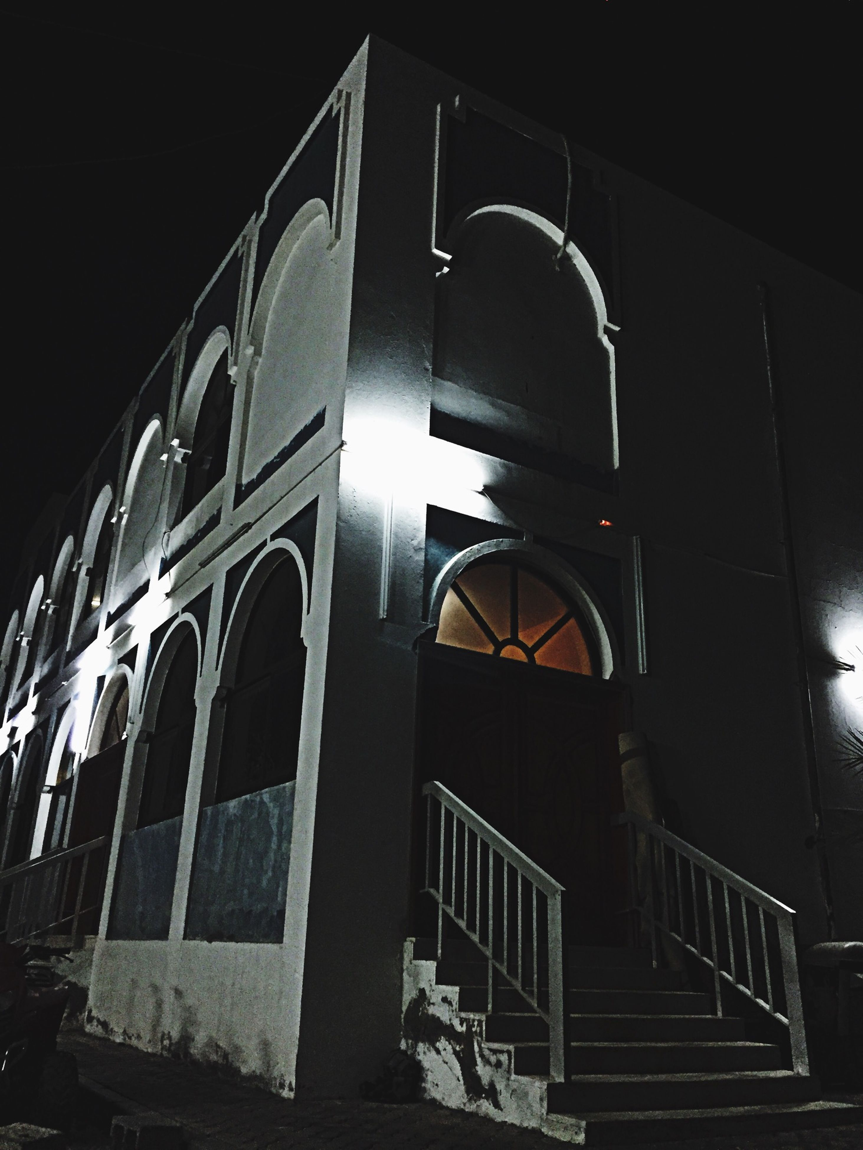 architecture, built structure, building exterior, low angle view, illuminated, night, building, window, arch, no people, lighting equipment, railing, outdoors, city, sky, exterior, modern, residential building, architectural feature