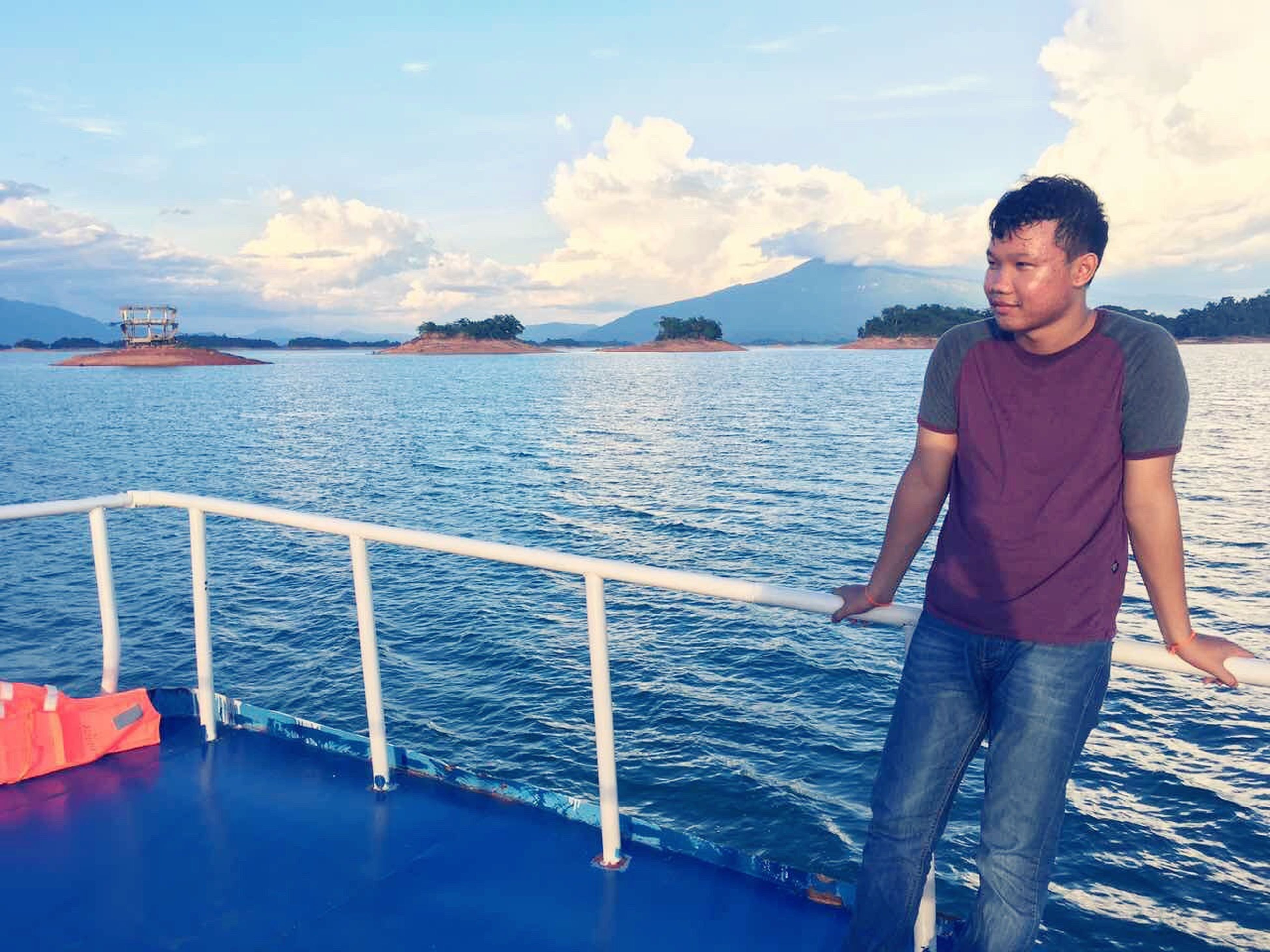 water, sea, lifestyles, sky, leisure activity, standing, casual clothing, railing, full length, nautical vessel, person, vacations, blue, pier, nature, scenics, travel, three quarter length