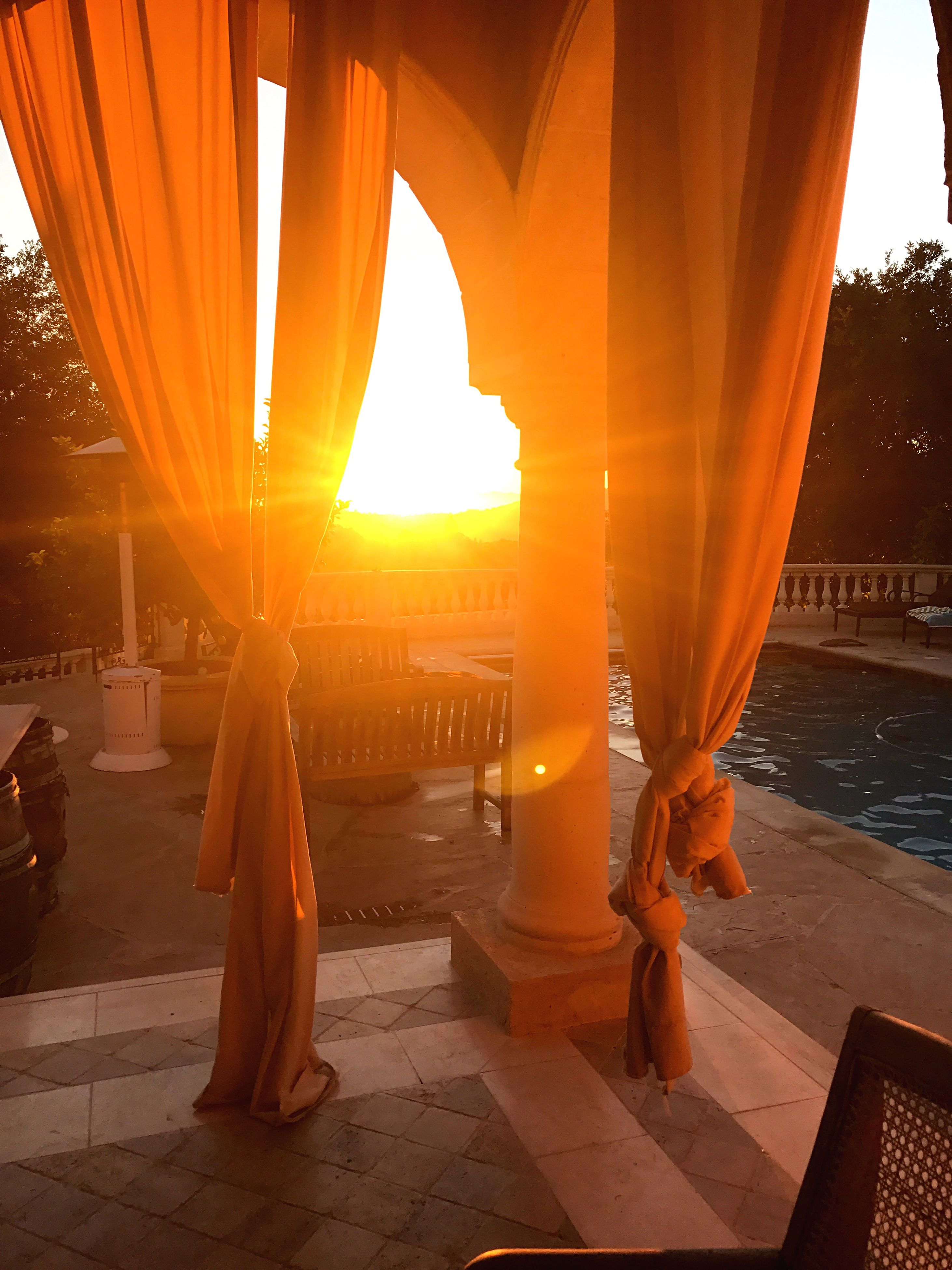 orange color, sunset, sunlight, curtain, architectural column, sun, sea, architecture, water, no people, outdoors, sky, day, nature, beauty in nature