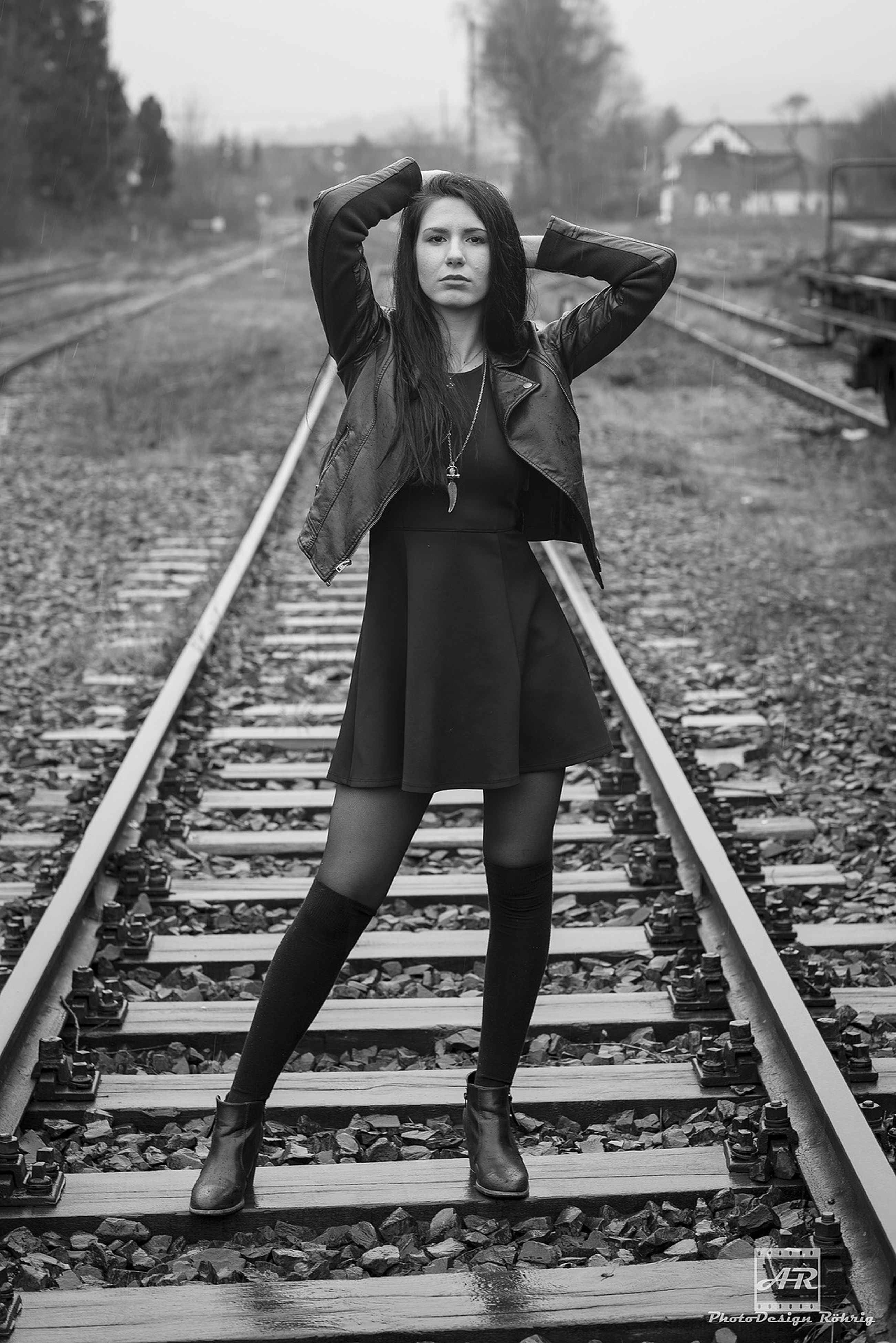 young adult, lifestyles, person, full length, casual clothing, young women, leisure activity, standing, front view, looking at camera, portrait, railroad track, transportation, three quarter length, railing, smiling, day