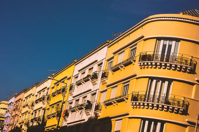 Architecture Balcony Blue Building Building Exterior Built Structure City Clear Sky Day House Low Angle View Multi Colored No People Outdoors Residential Building Residential Structure Sky Sunlight Window Yellow