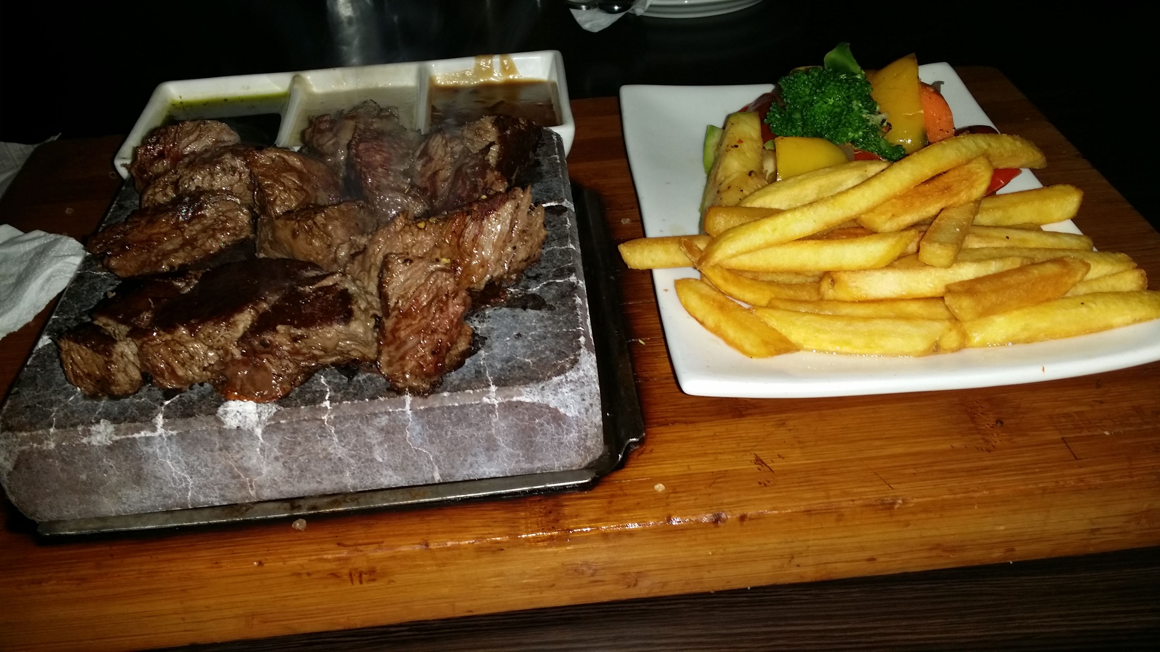 food and drink, food, indoors, freshness, ready-to-eat, still life, table, healthy eating, meat, meal, plate, high angle view, slice, indulgence, close-up, serving size, cutting board, fork, french fries