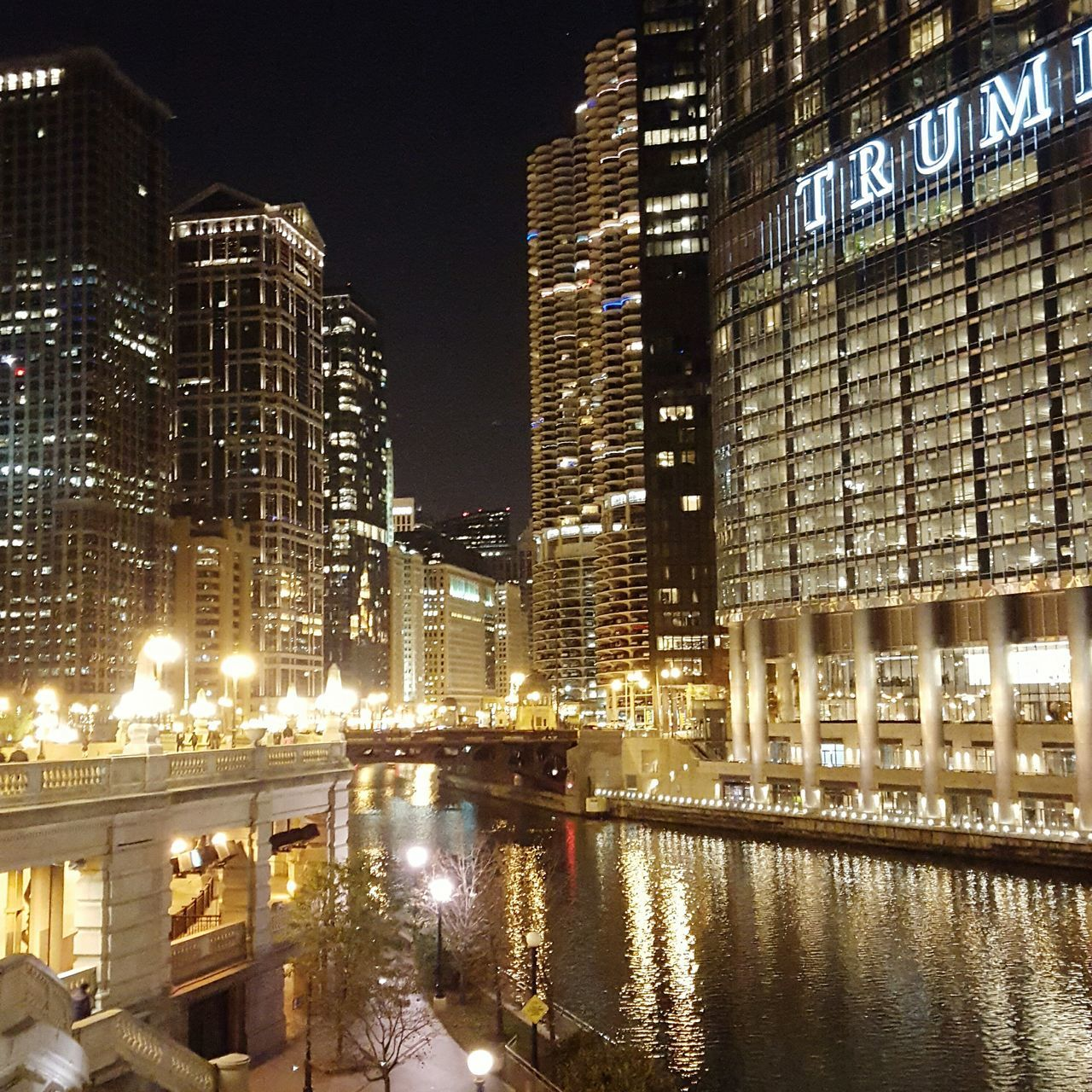 architecture, building exterior, built structure, illuminated, night, city, skyscraper, modern, river, reflection, water, no people, outdoors, cityscape, sky