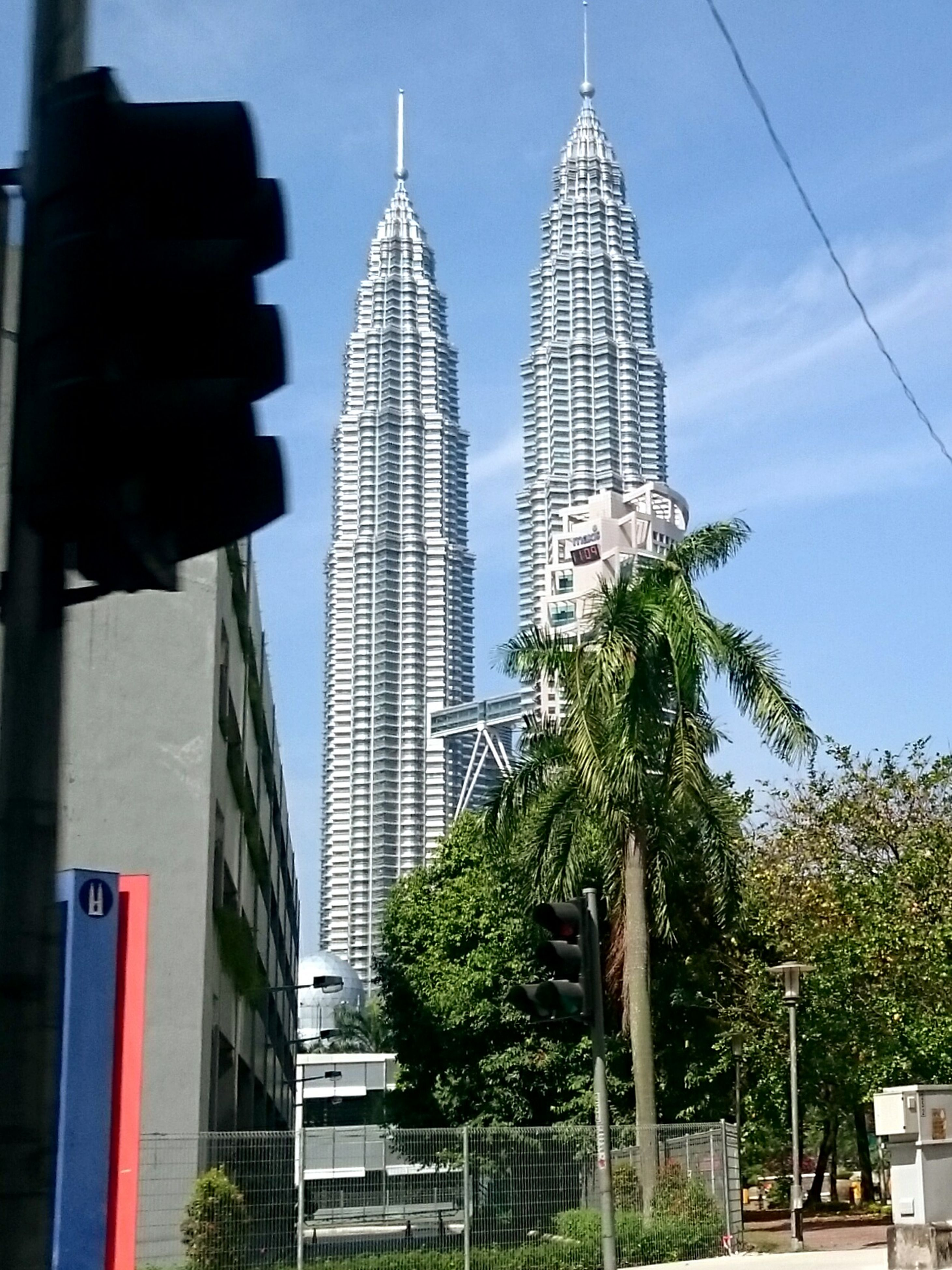 architecture, building exterior, built structure, tall - high, tower, low angle view, city, skyscraper, modern, office building, sky, spire, tree, famous place, travel destinations, capital cities, tall, building, day, city life