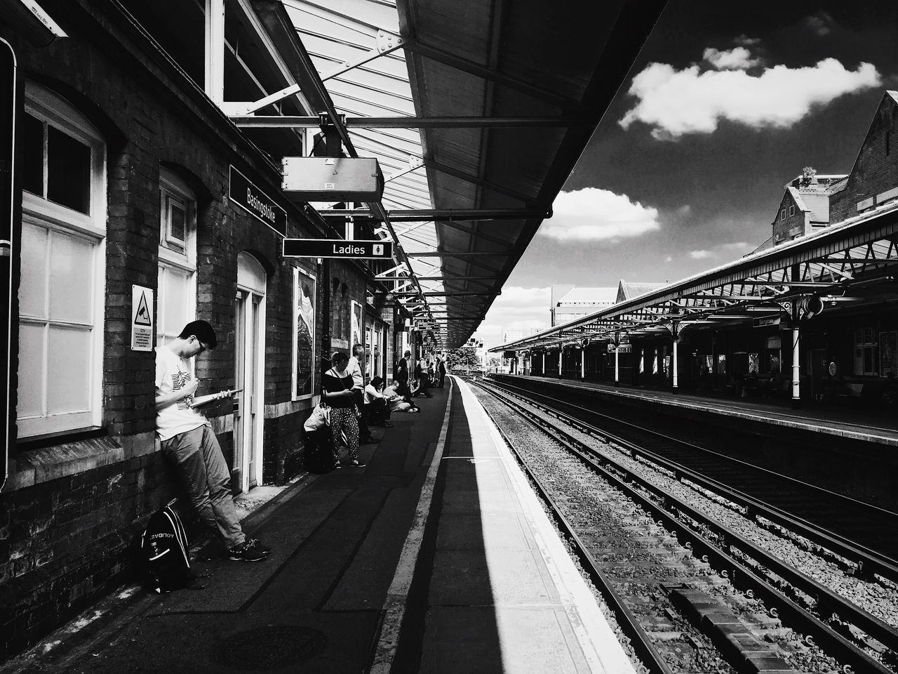 transportation, railroad track, one person, real people, rail transportation, public transportation, mode of transport, railroad station platform, day, architecture, full length, sky, men, built structure, outdoors, lifestyles, building exterior, people