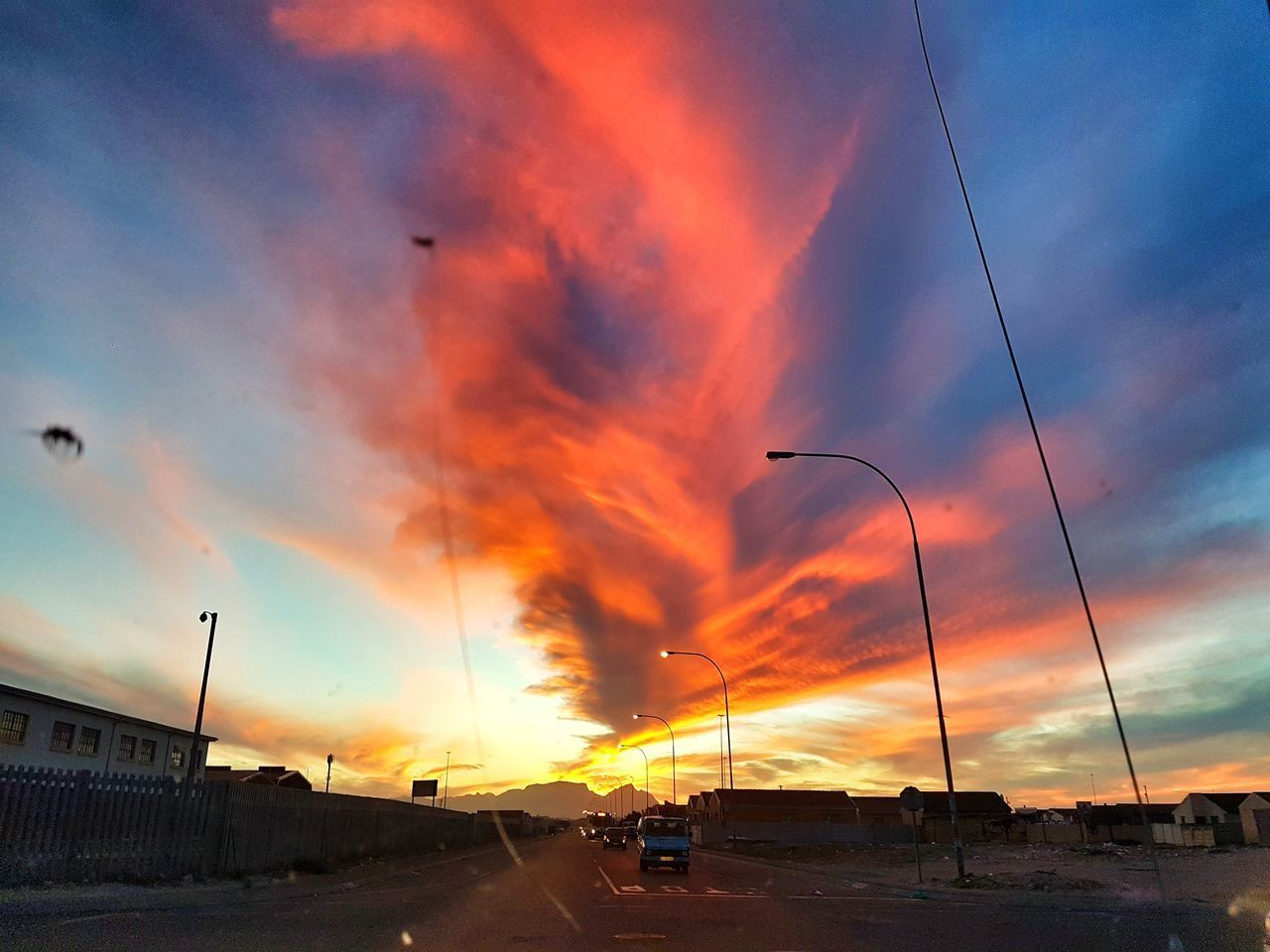 sunset, cloud - sky, sky, orange color, dramatic sky, car, land vehicle, transportation, mode of transport, road, nature, built structure, outdoors, architecture, building exterior, beauty in nature, no people, city, day