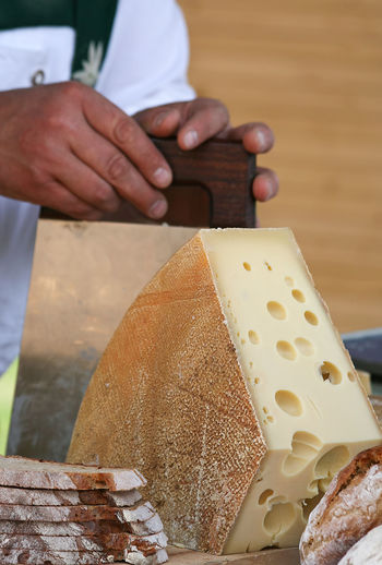 Half loaf of swiss hard cheese Knife Market Vegetarian Food Bread Cheese Cutter Close-up Dairy Product Delicatessen Emmentaler Food Food And Drink Hard Cheese Healthy Eating Holding Human Body Part Human Hand Loaf Of Cheese Occupation One Person Ready-to-eat Swiss Switzerland