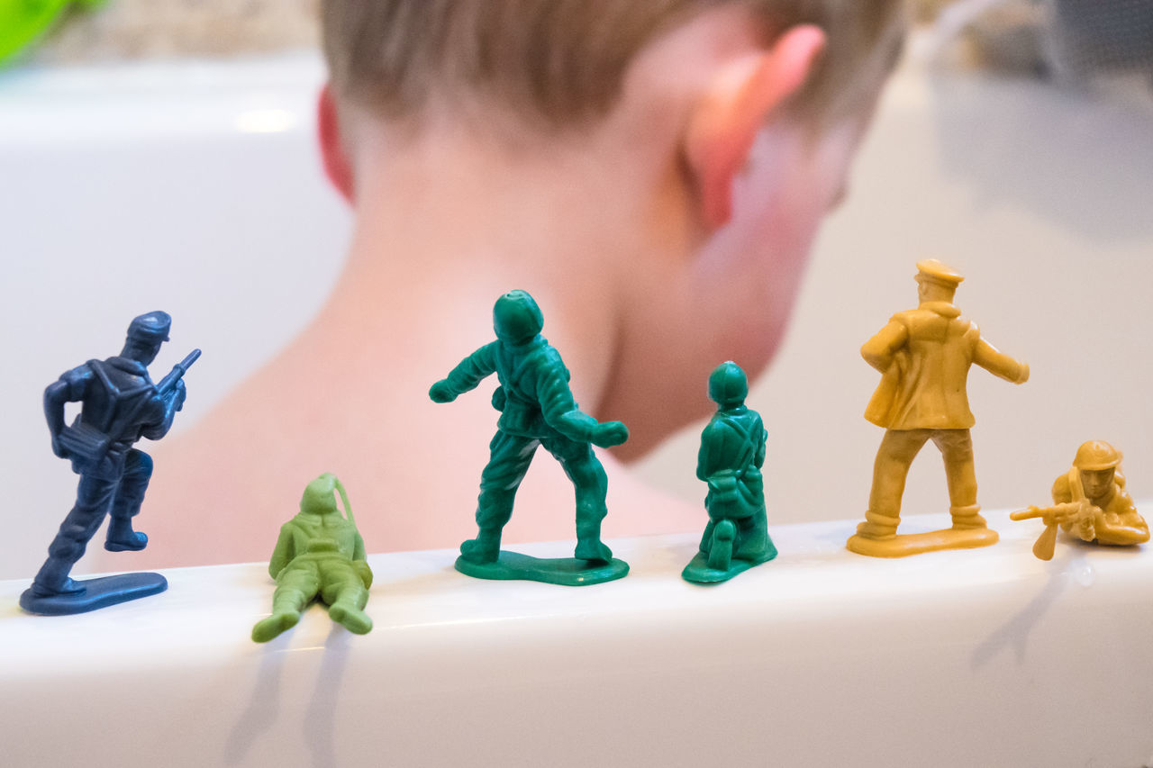 Close-Up Of Boy By Toy Soldiers On Bathtub