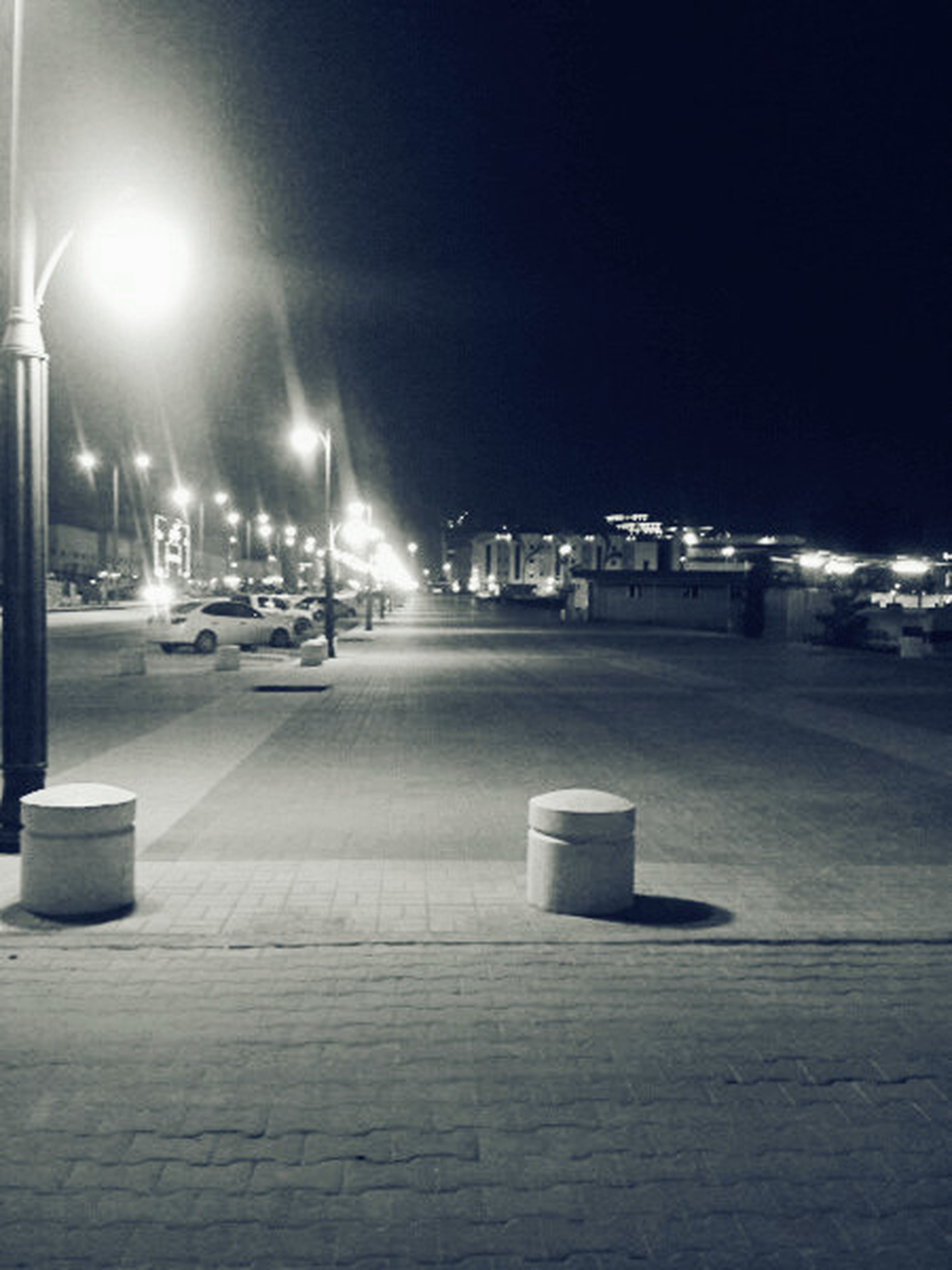 illuminated, night, transportation, street light, street, building exterior, city, architecture, car, built structure, road, the way forward, land vehicle, lighting equipment, mode of transport, city street, sky, road marking, diminishing perspective, city life