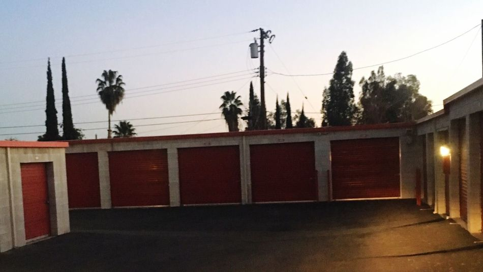 Storage Unit Built Structure Architecture Building Exterior Cable Low Angle View Outdoors No People Day Power Line  Electricity  Power Supply Clear Sky Tree Connection Sky Electricity Pylon Storage Facility Garage Doors Orange Door