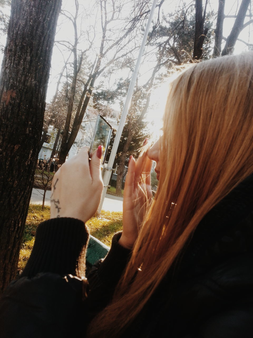 real people, tree, leisure activity, photographing, tree trunk, cellphone, one person, day, technology, lifestyles, photography themes, wireless technology, outdoors, human hand, nature, close-up