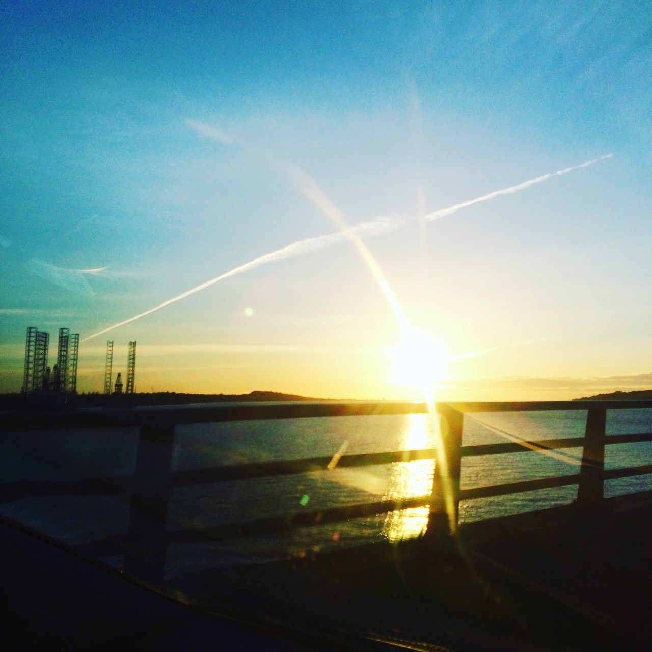 sun, sunlight, sunbeam, sunset, lens flare, nature, scenics, beauty in nature, no people, sky, water, tranquility, outdoors, tranquil scene, built structure, sea, silhouette, architecture, travel destinations, building exterior, day, sunshine, refraction, horizon over water, vapor trail