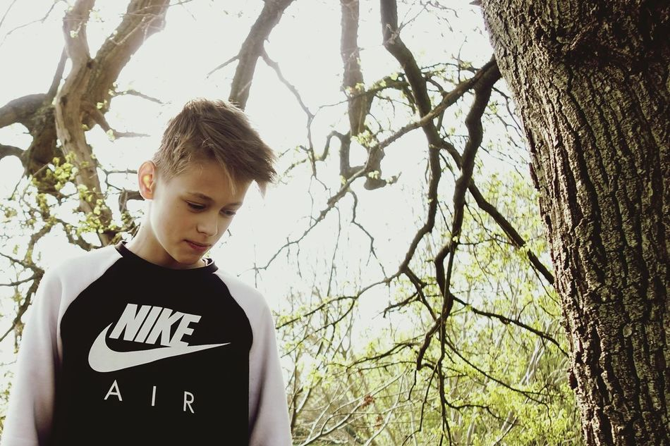 One Person Blond Hair Tree Tree Trunk Teenager Teenage Boy Looking Down Day Outdoors