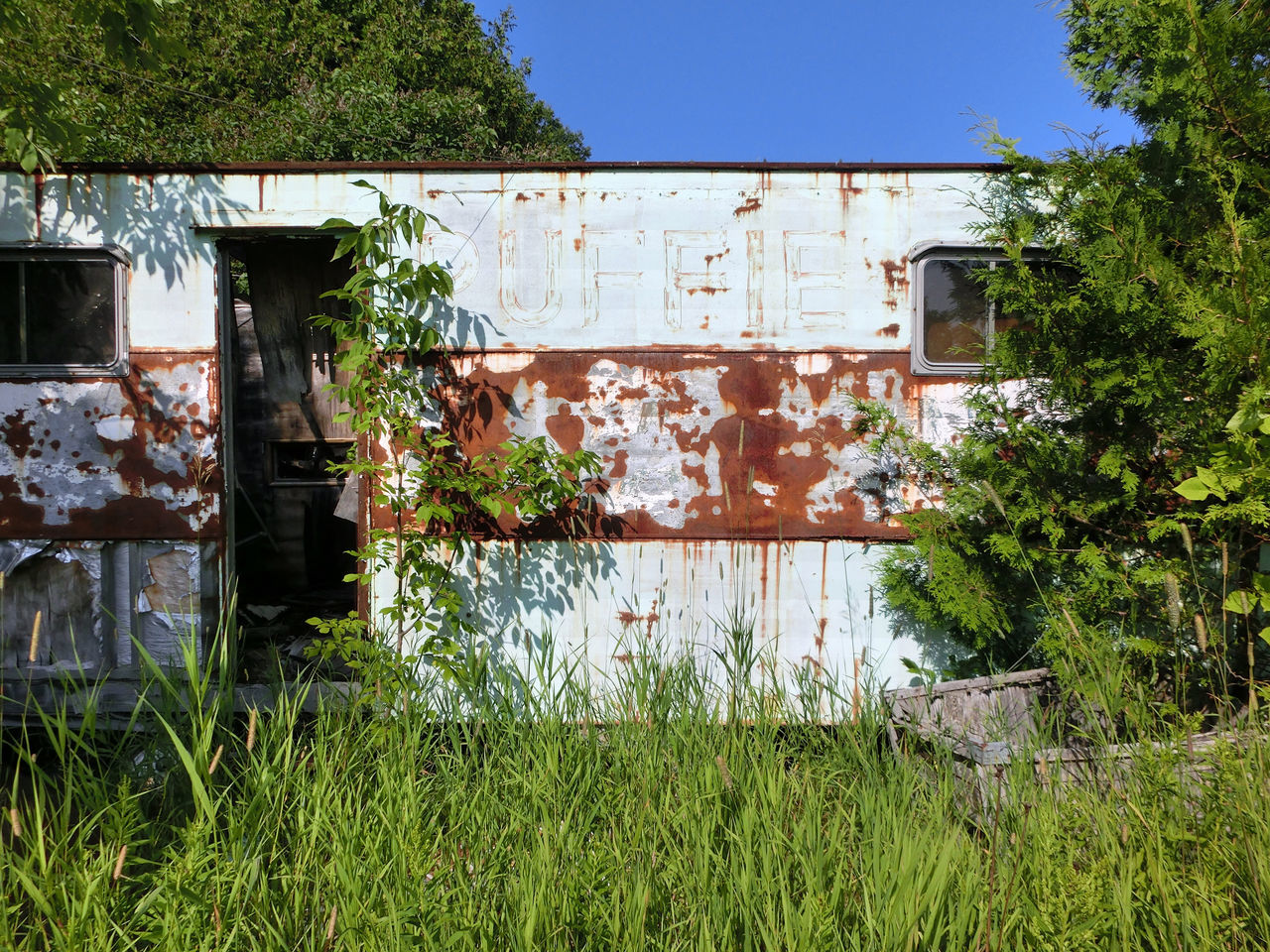 Abandoned Places Architecture Blue Building Exterior Built Structure Day Deterioration Grass Grassy Green Color Growing Growth House Nature No People Old Outdoors Plant Residential Structure Run-down Sky Sunny Trailor Tranquility