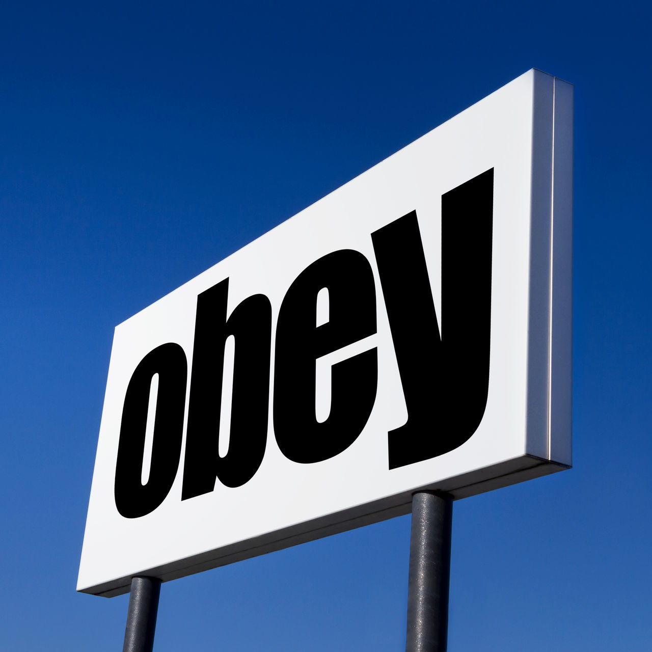 Horizontal billboard with the order to OBEY, against irreal blue sky. Abstract concept of consumerism, human mind control, power of corporations and lobbies. Ad Banking Business Command Conceptual Consumerism Control Enslavement Future Global Lobbies Lobby Message Obedience OBEY Order Power Sign Sky Stock Subliminal Text White Word