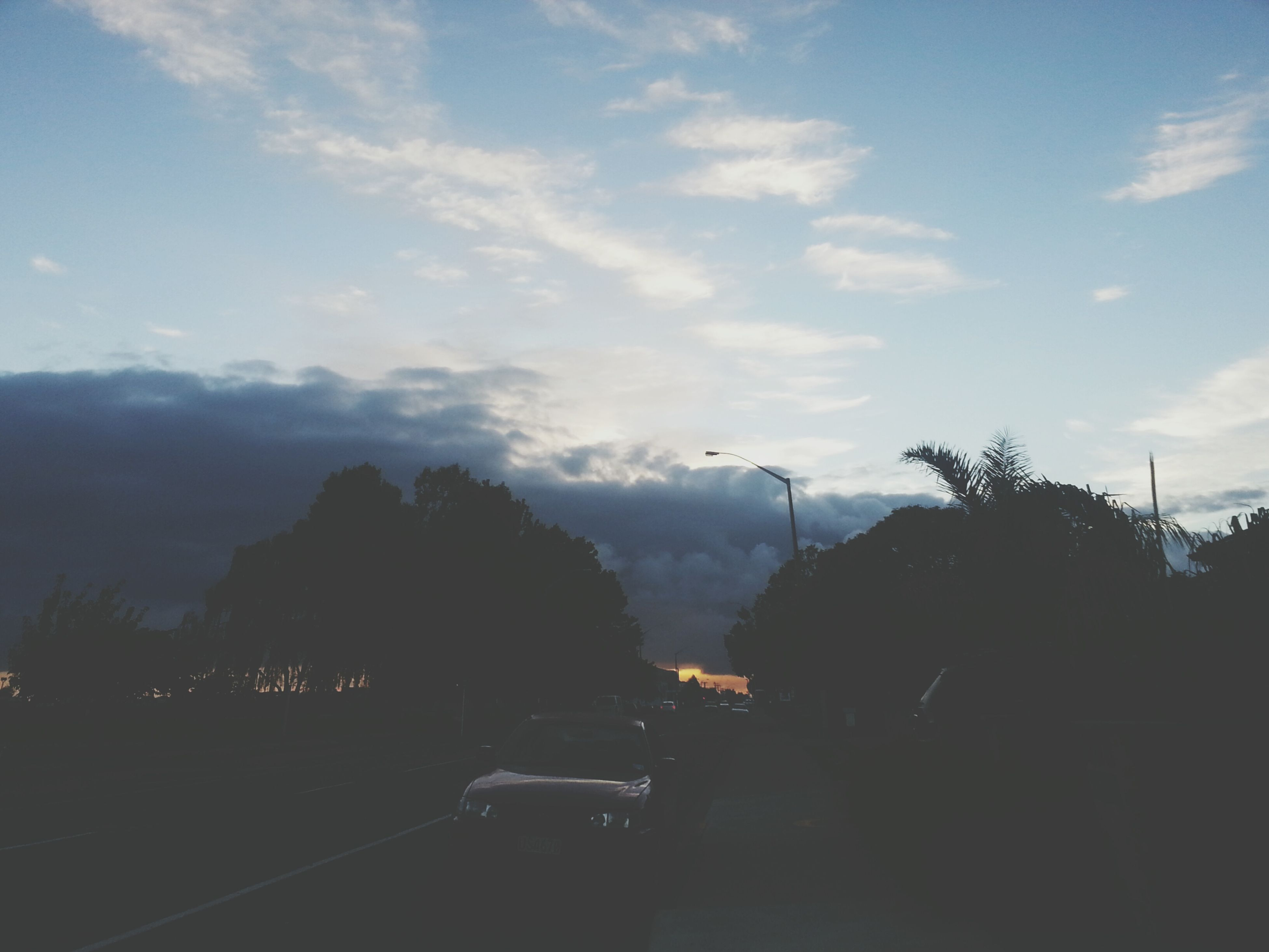 sky, transportation, silhouette, car, mode of transport, cloud - sky, road, land vehicle, tree, cloud, dusk, sunset, nature, mountain, scenics, street, beauty in nature, outdoors, tranquility, cloudy
