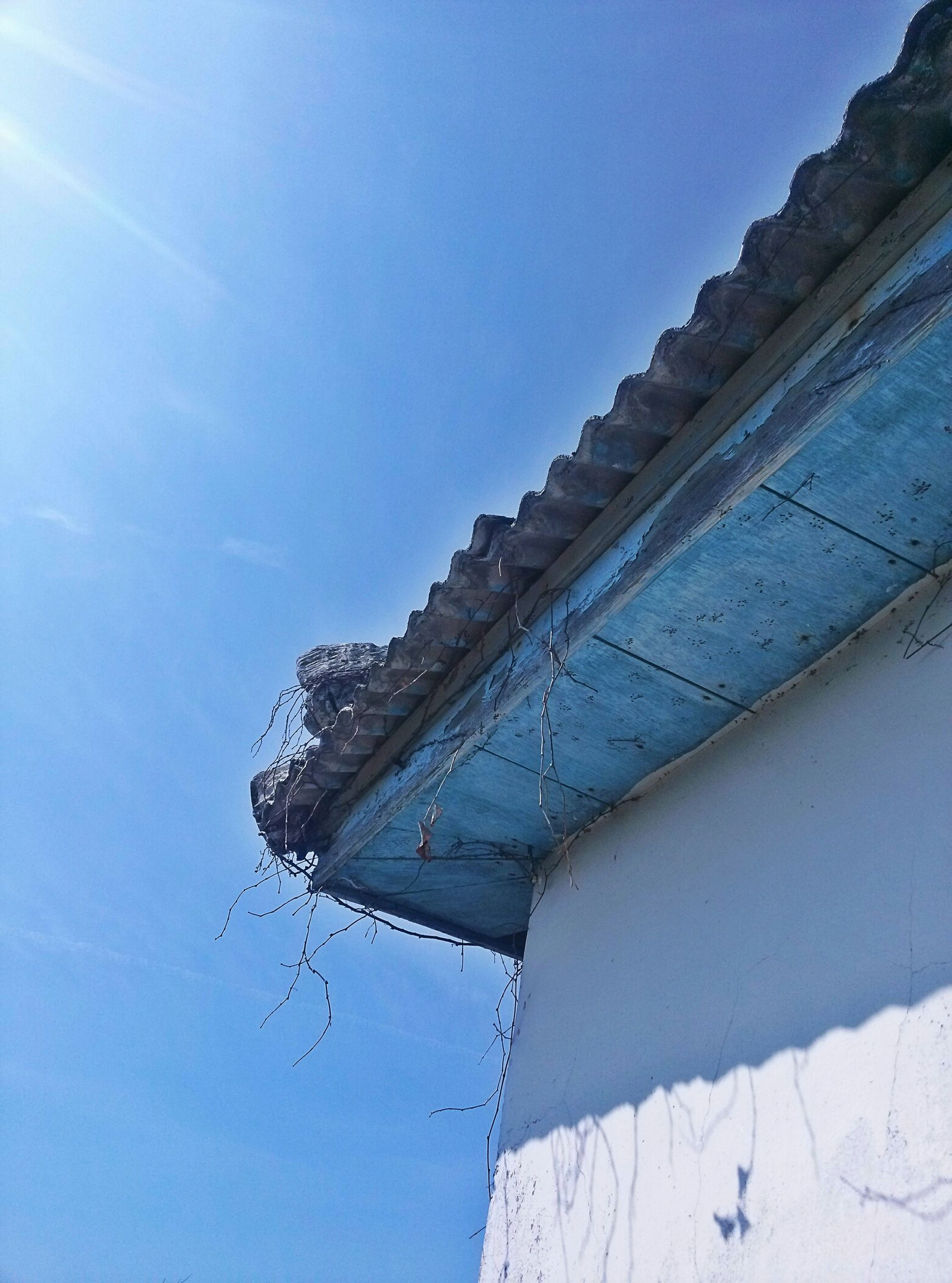 low angle view, blue, built structure, building exterior, architecture, clear sky, sky, roof, high section, day, outdoors, house, sunlight, no people, copy space, tilt, part of, building, nature, damaged