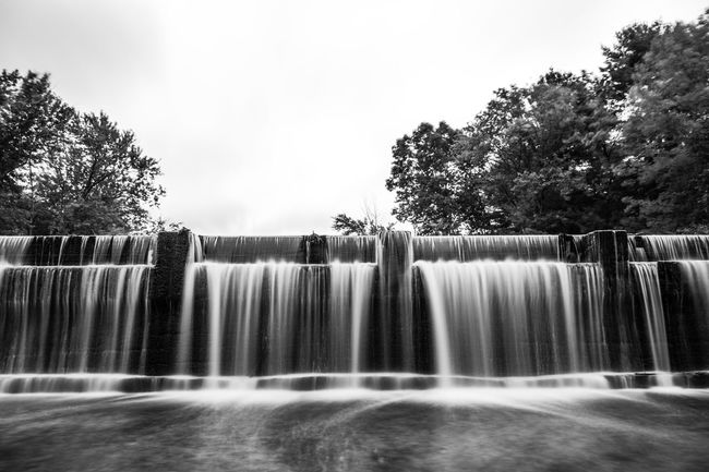 Wide long exposure of Nashua River dam on the Shirley/Ayer town line in Massachusetts Beauty In Nature Black & White Black And White Blackandwhite Blurred Motion Dam Flowing Flowing Water Growth Long Exposure Longexposure Longexposurephotography Lush Foliage Motion Nature No People Outdoors Purity Scenics Splashing Spraying Monochrome Photography Water Waterfall Waterfront